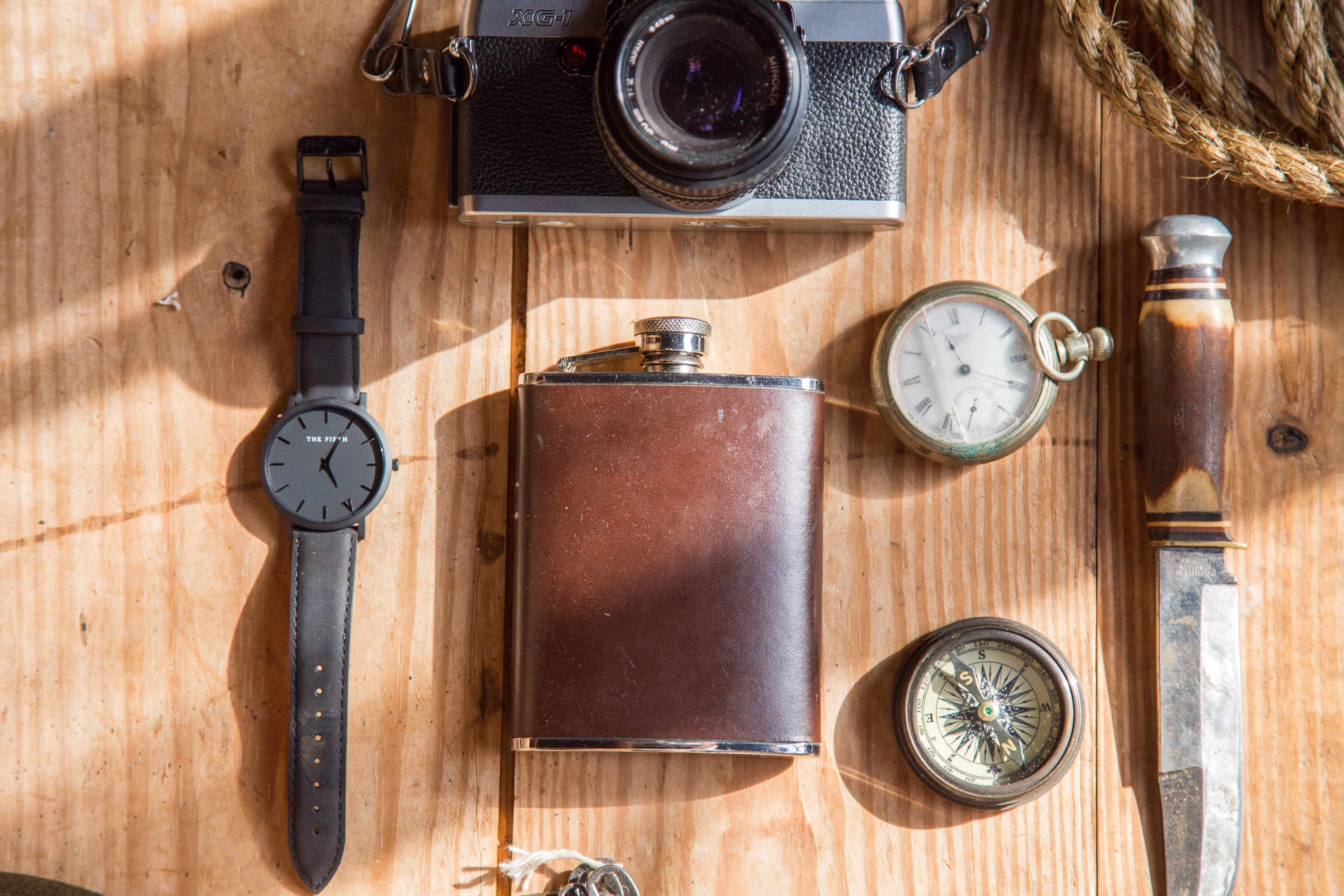 Brown wine flask near lomo camera watch knife and pocket watches on able photo