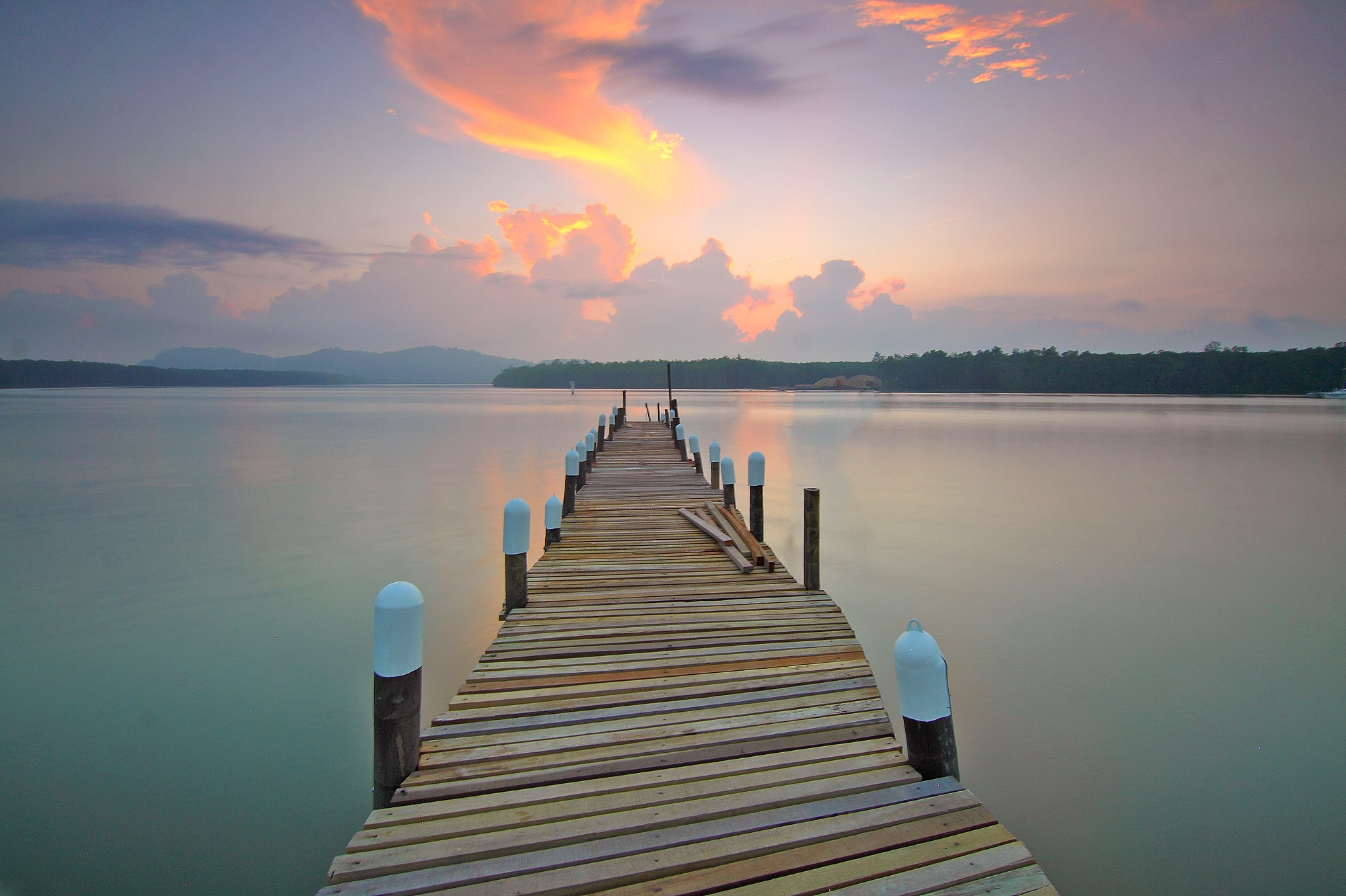 Brown wooden footbridge on body of water during sunrise photo
