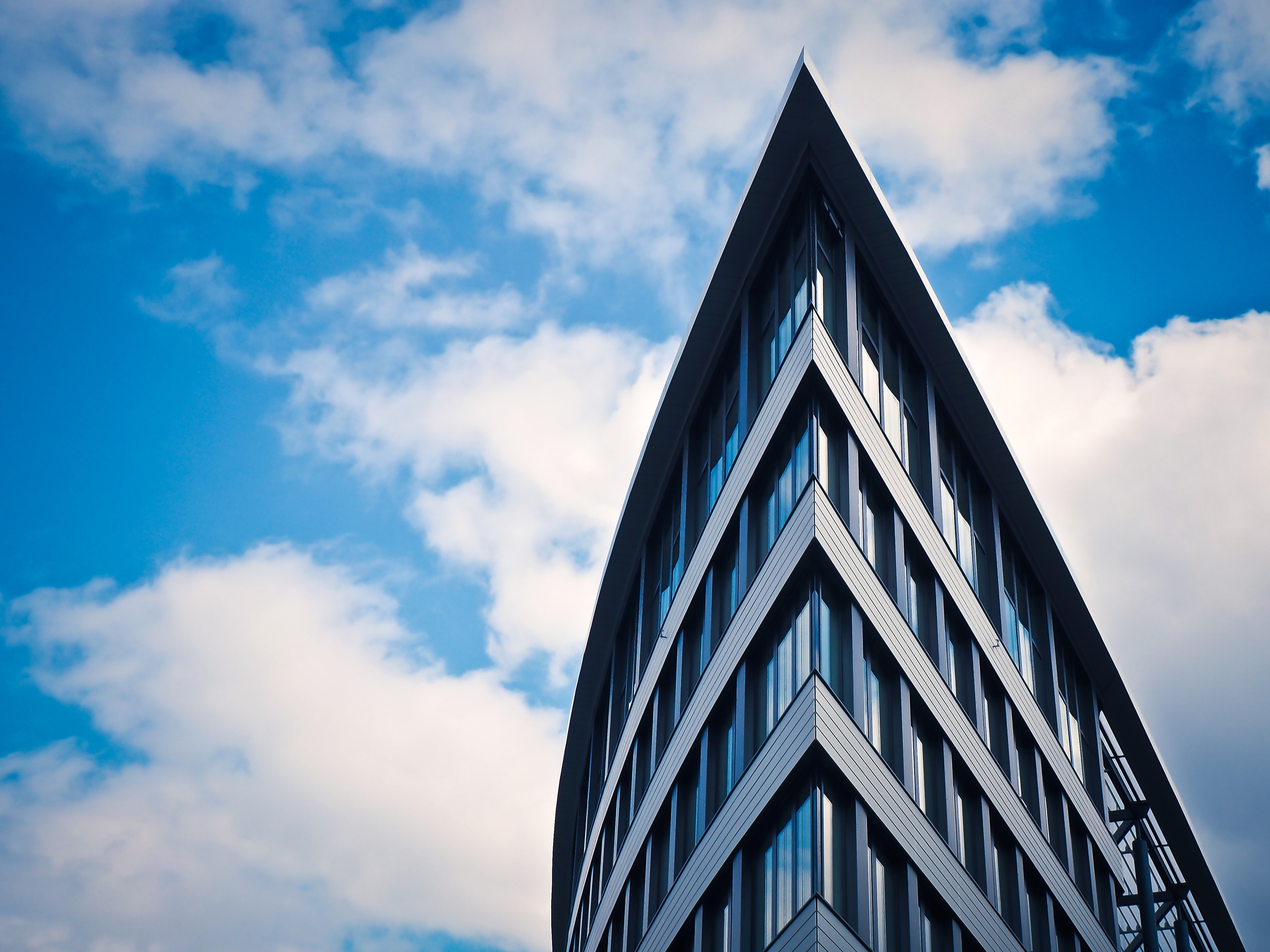 Low Angle View of Building Against Cloudy Sky · Free Stock Photo