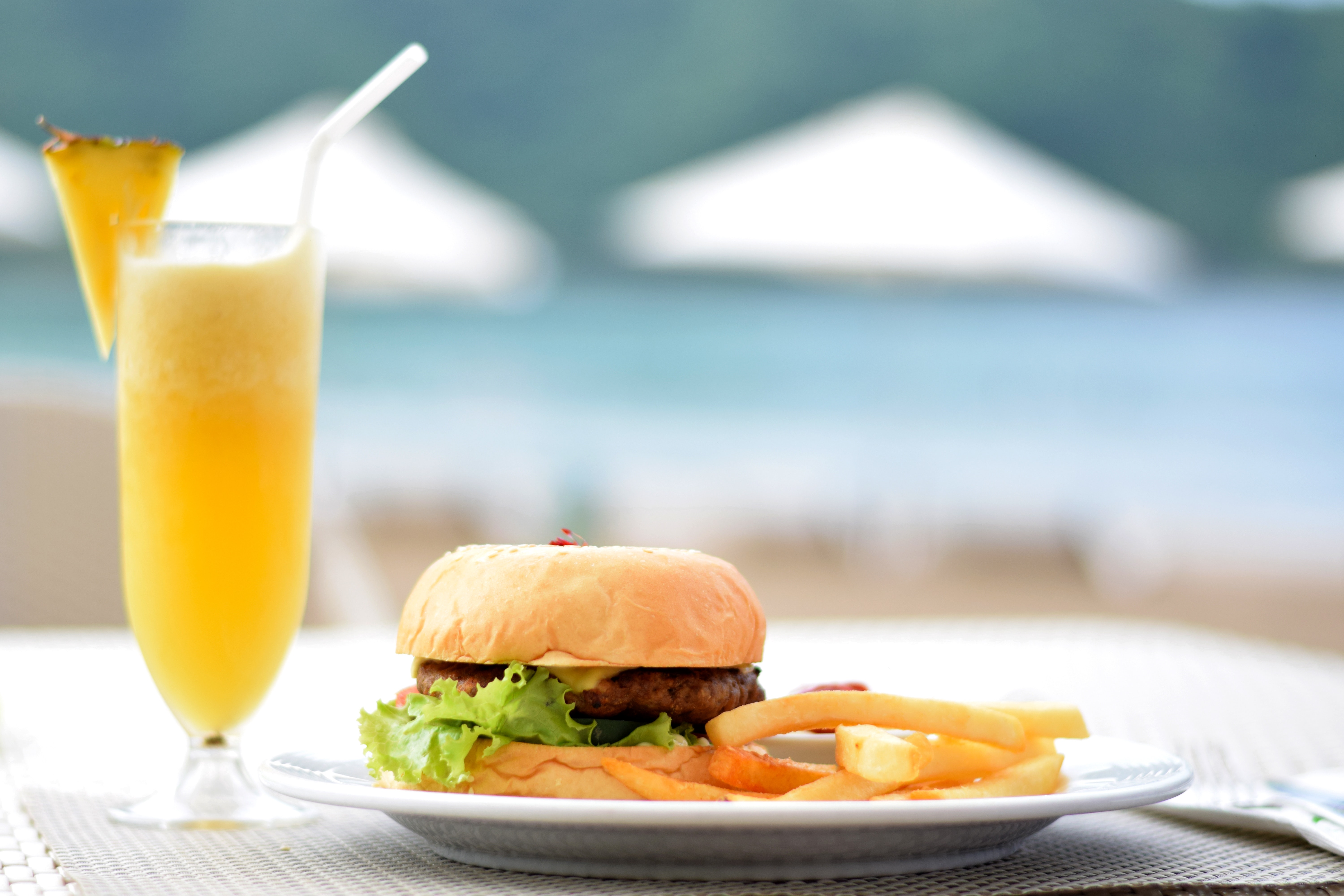 Burger with lettuce and fries on plate beside pineapple juice photo