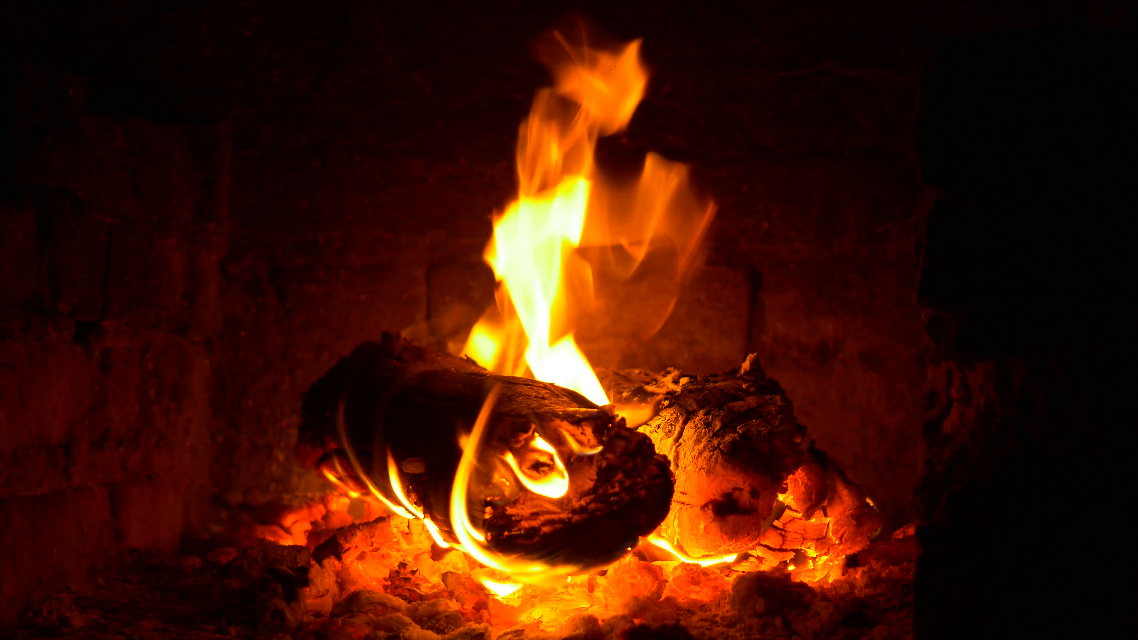 Flames of fire in fireplace in evening time 4K. Burning firewood ...