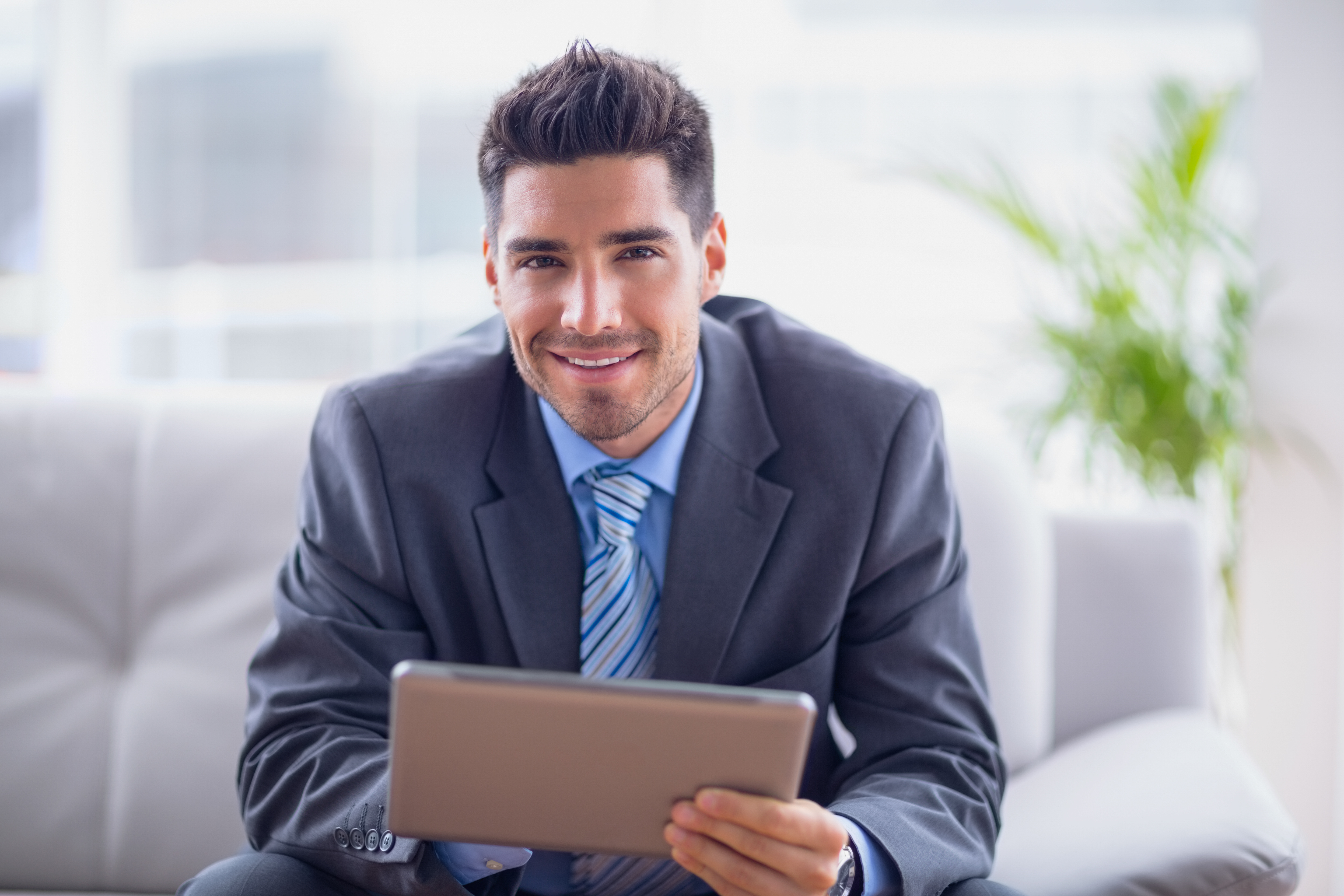 Businessman sitting on sofa using his tablet smiling at camera i ...