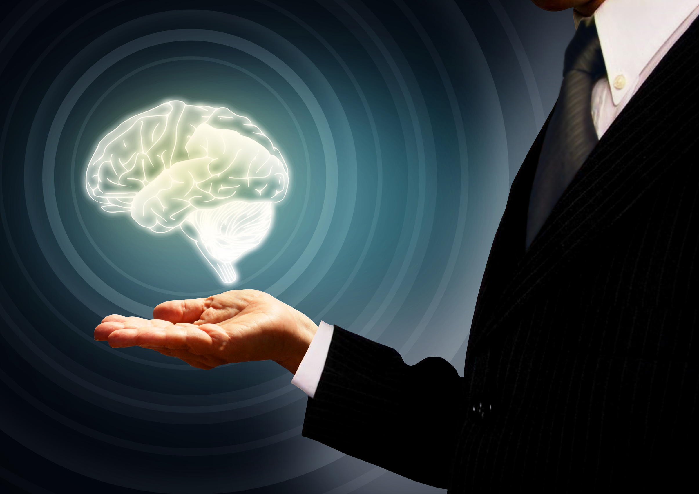 Businessman holding a brain in the palm - skills concept - concentric photo