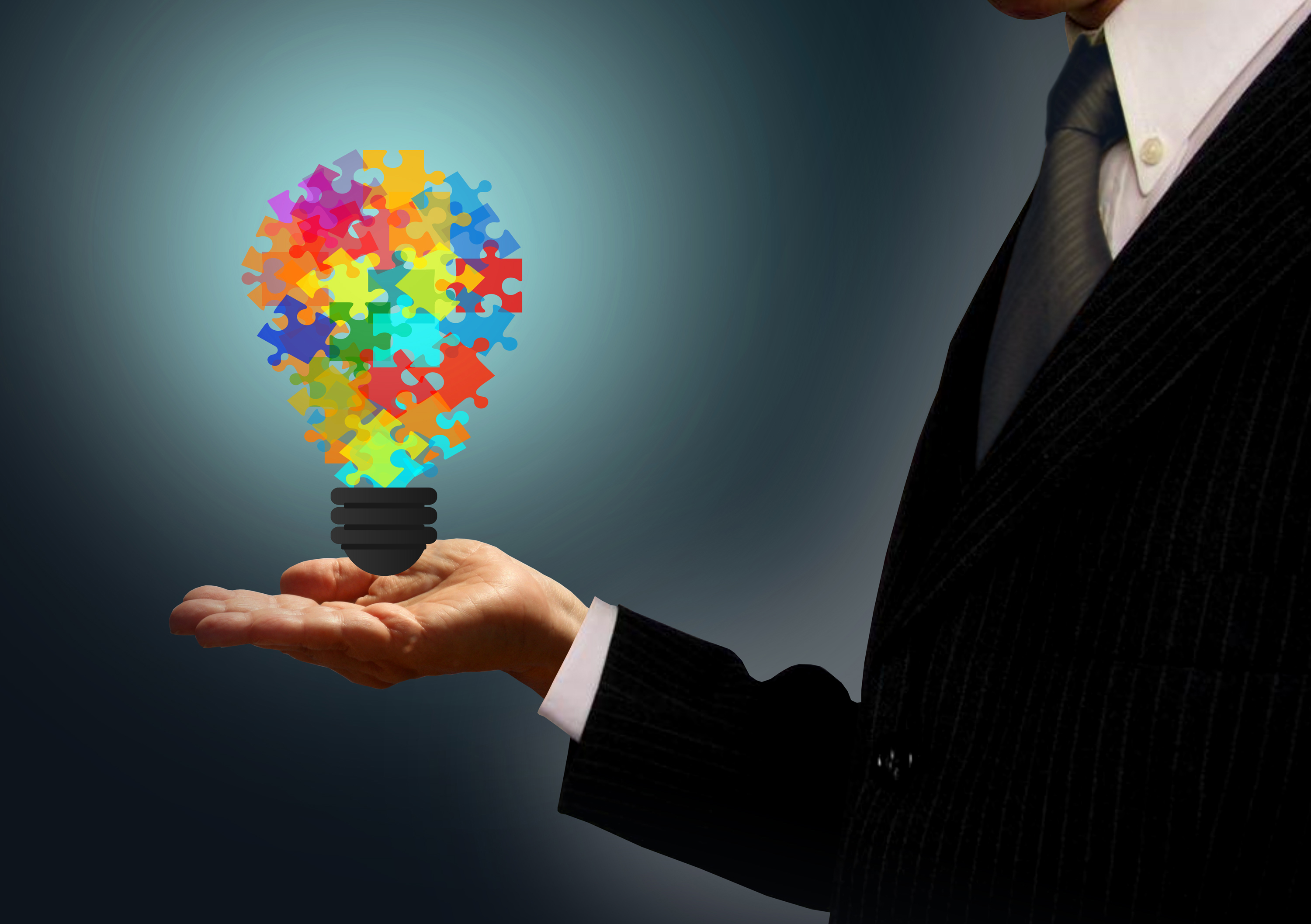 Businessman holding a jigsaw lightbulb - ideas and creativity concept photo