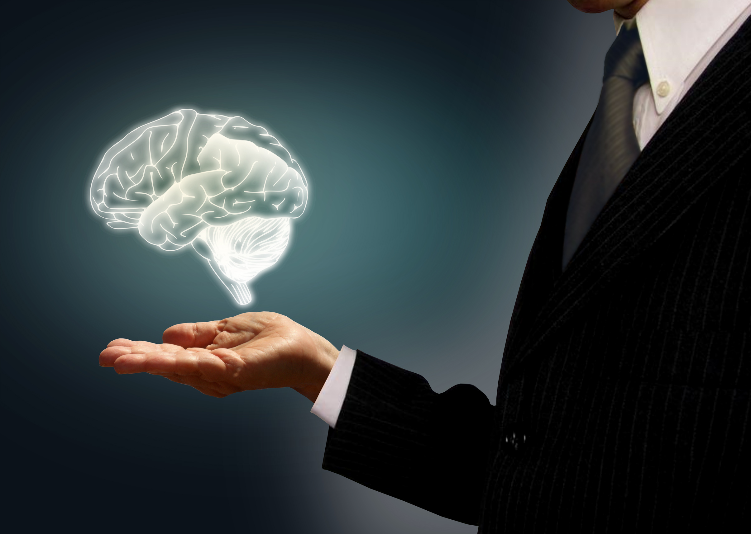Businessman holding a virtual brain in the palm - skills concept photo