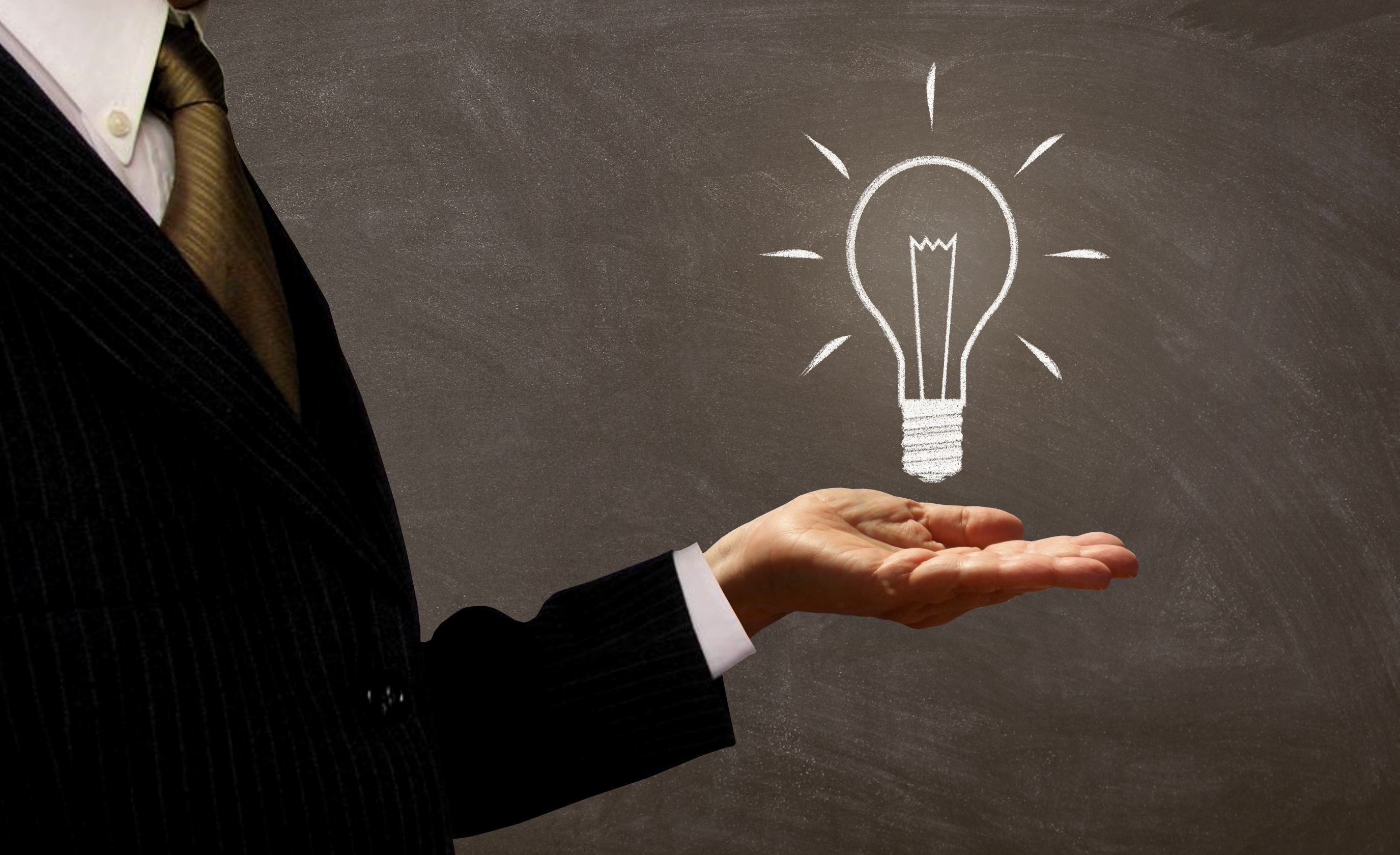 Businessman holding light bulb on chalkboard photo