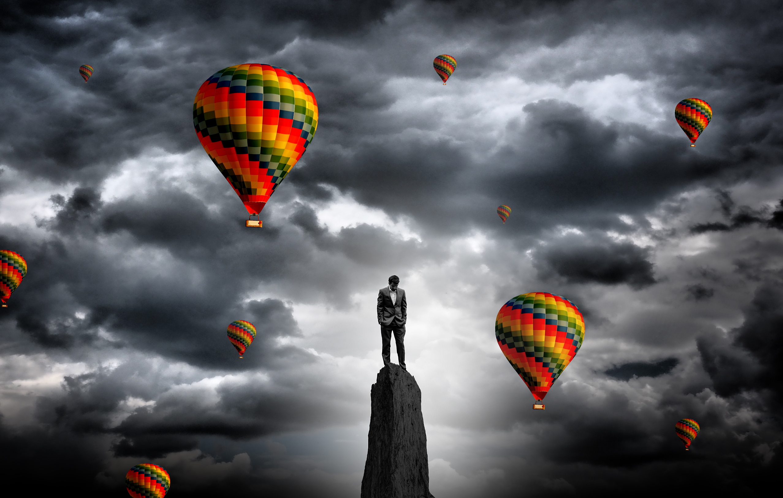 Businessman on the summit surrounded by hot air balloons photo
