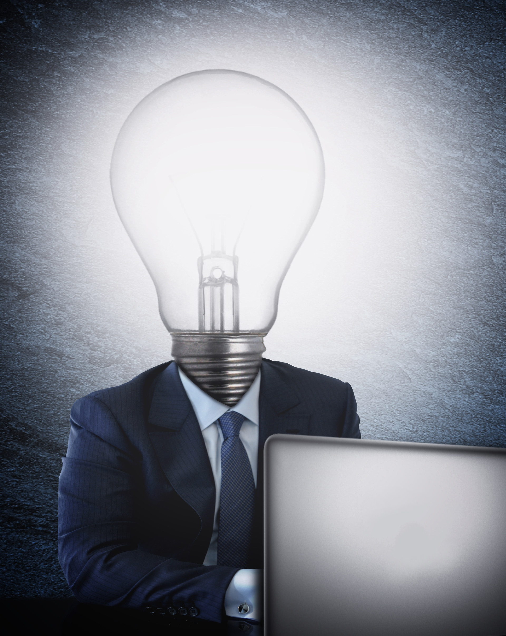 Businessman with lightbulb head in front of the computer photo