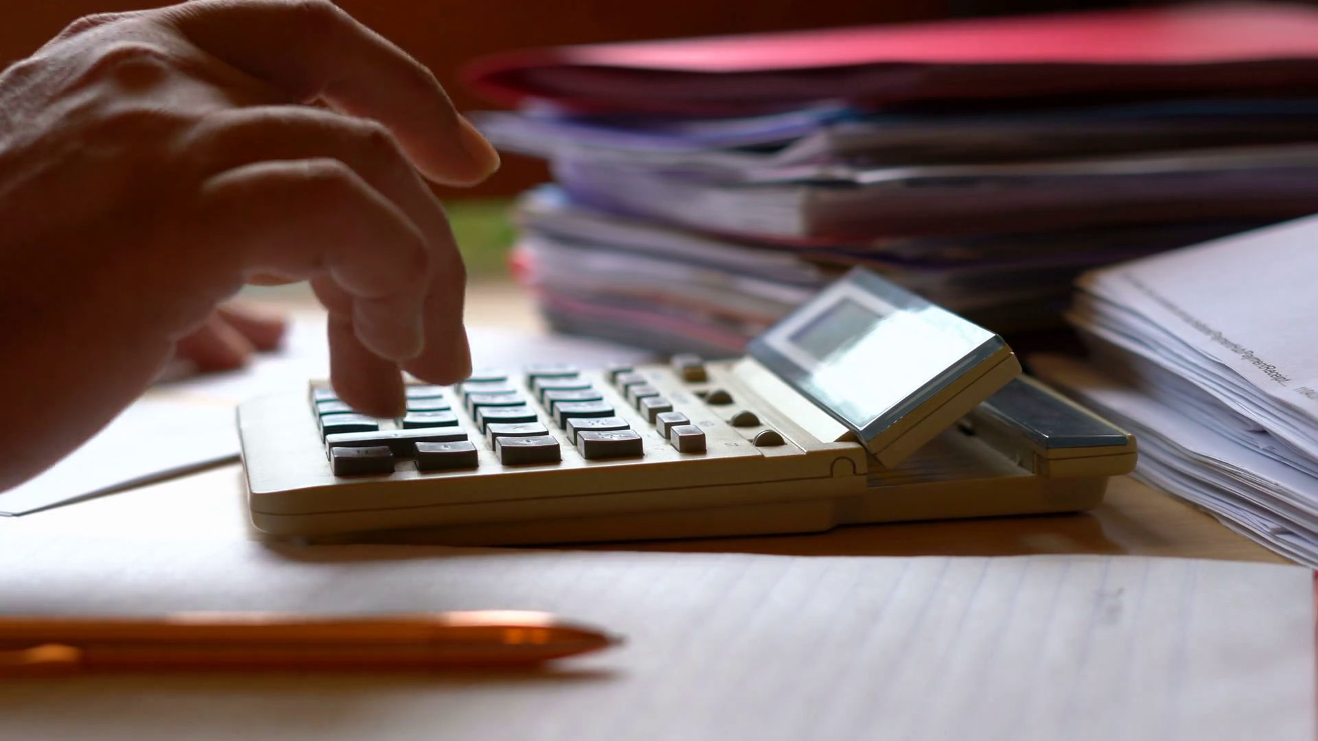 Accountant using calculator with stacks of paperwork and filing, in ...