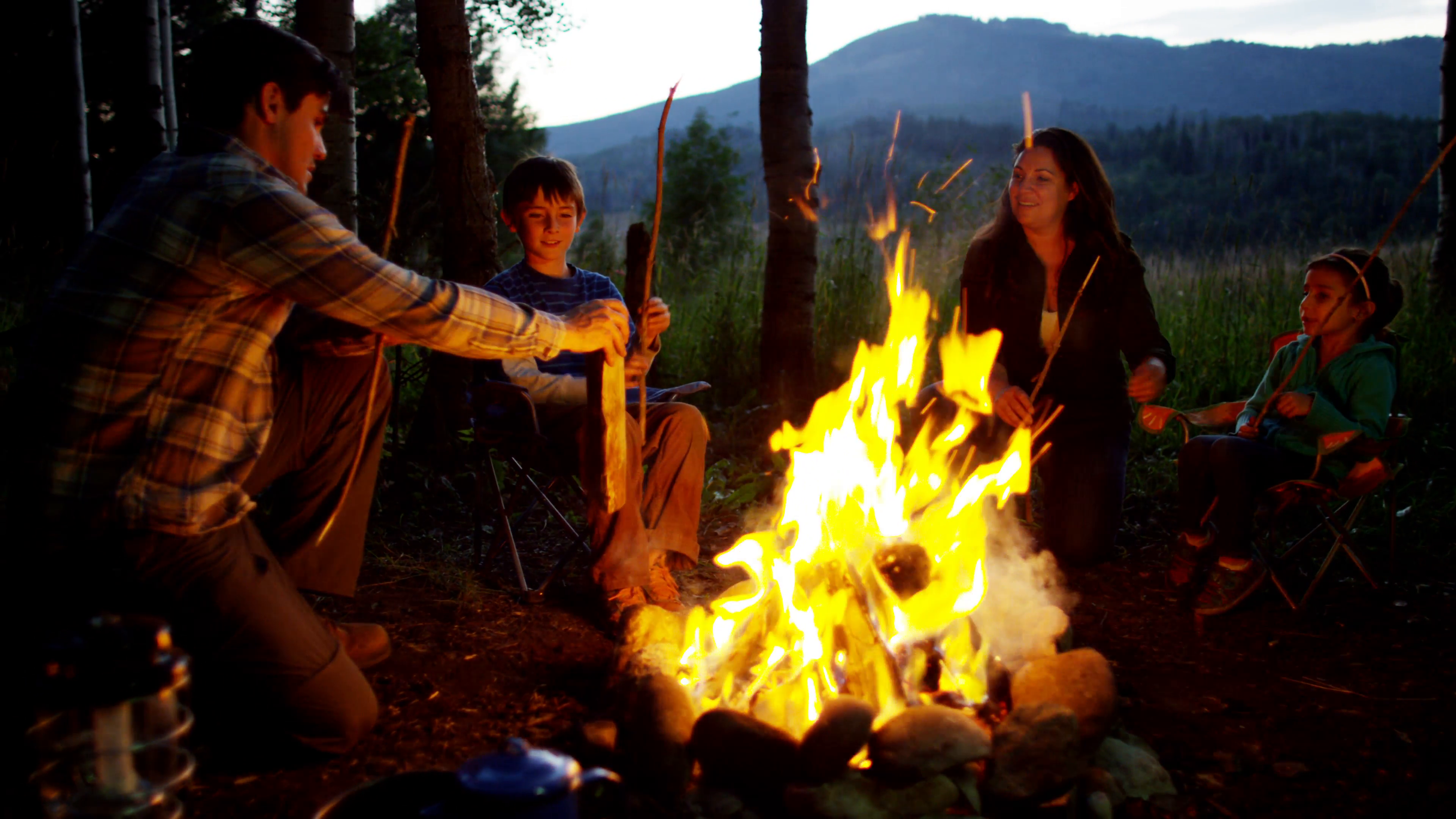 Happy American Caucasian family making campfire in nature on holiday ...