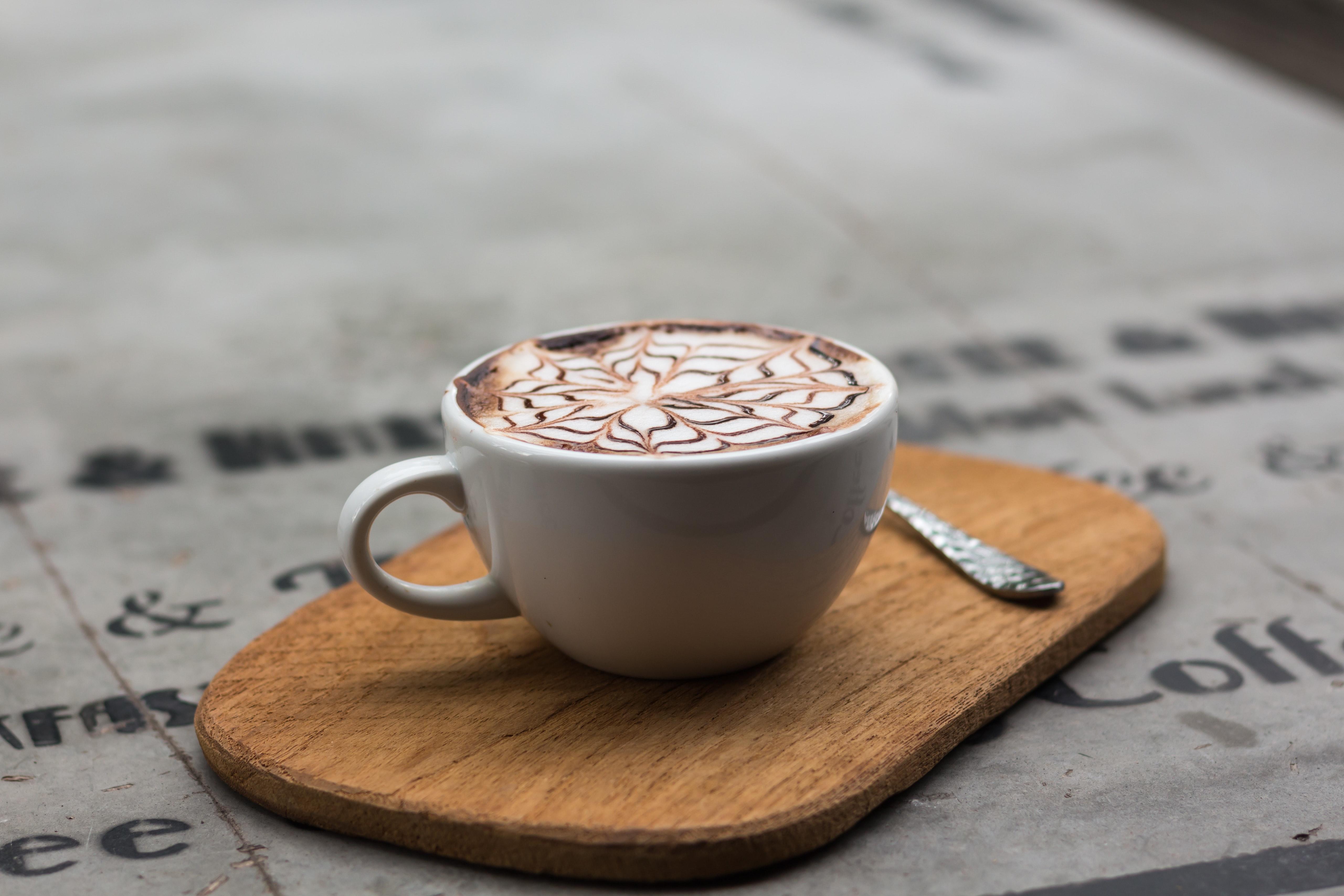Cappuccino in ceramic teacup beside teaspoon photo