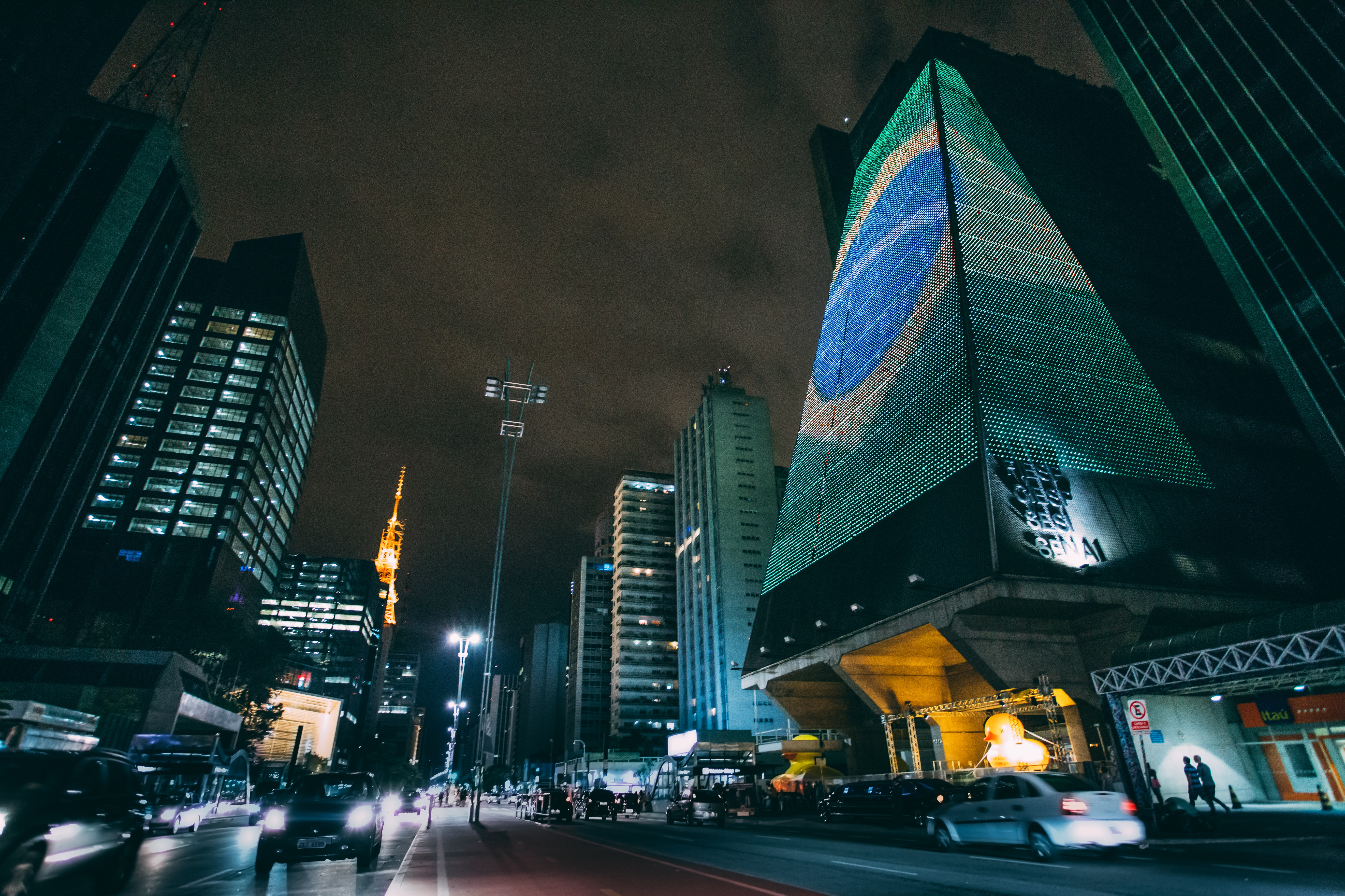 Cars traveling on road between buildings during nighttime photo