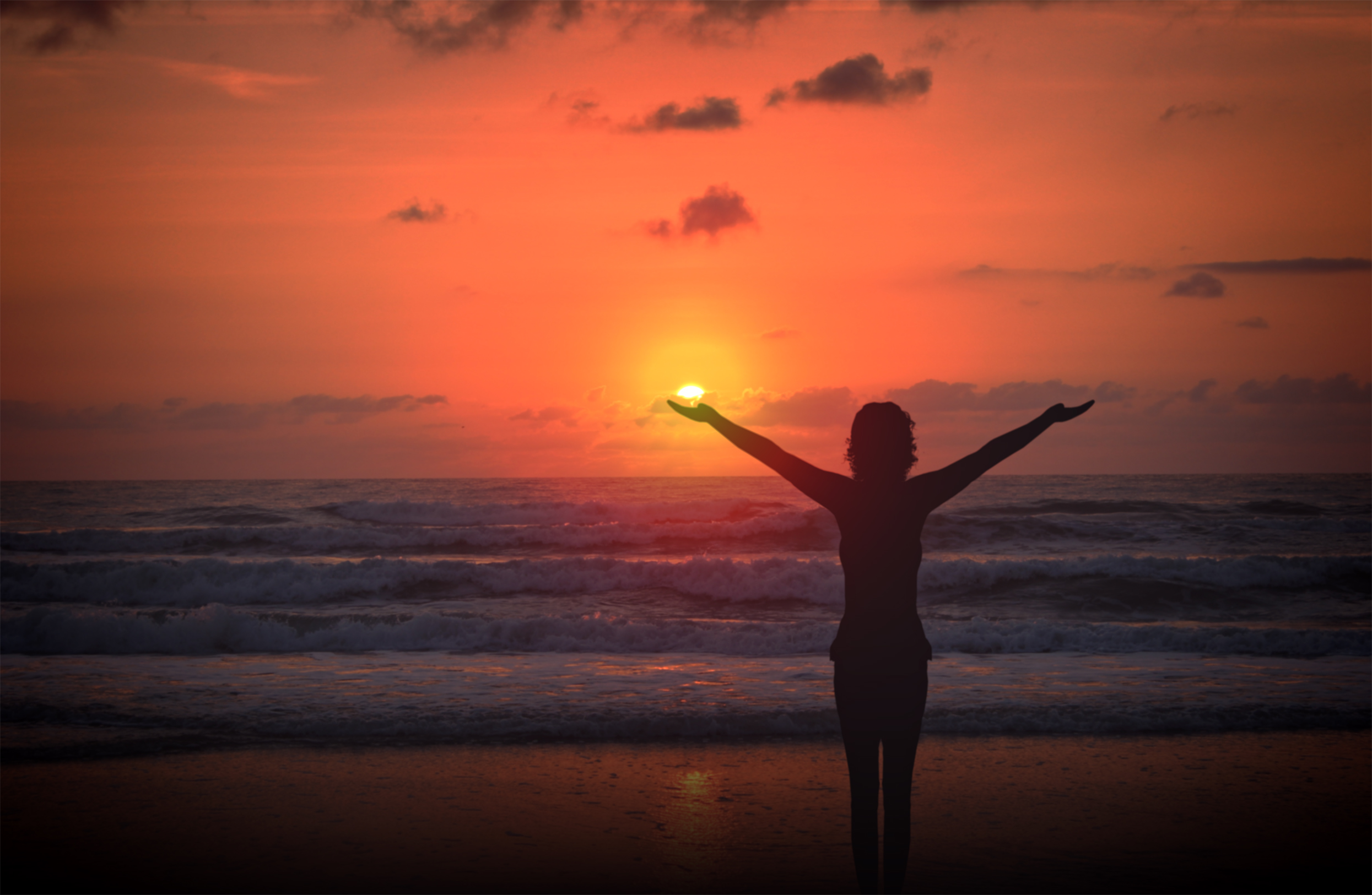 Celebrating life - a woman raises her arms at sunset photo