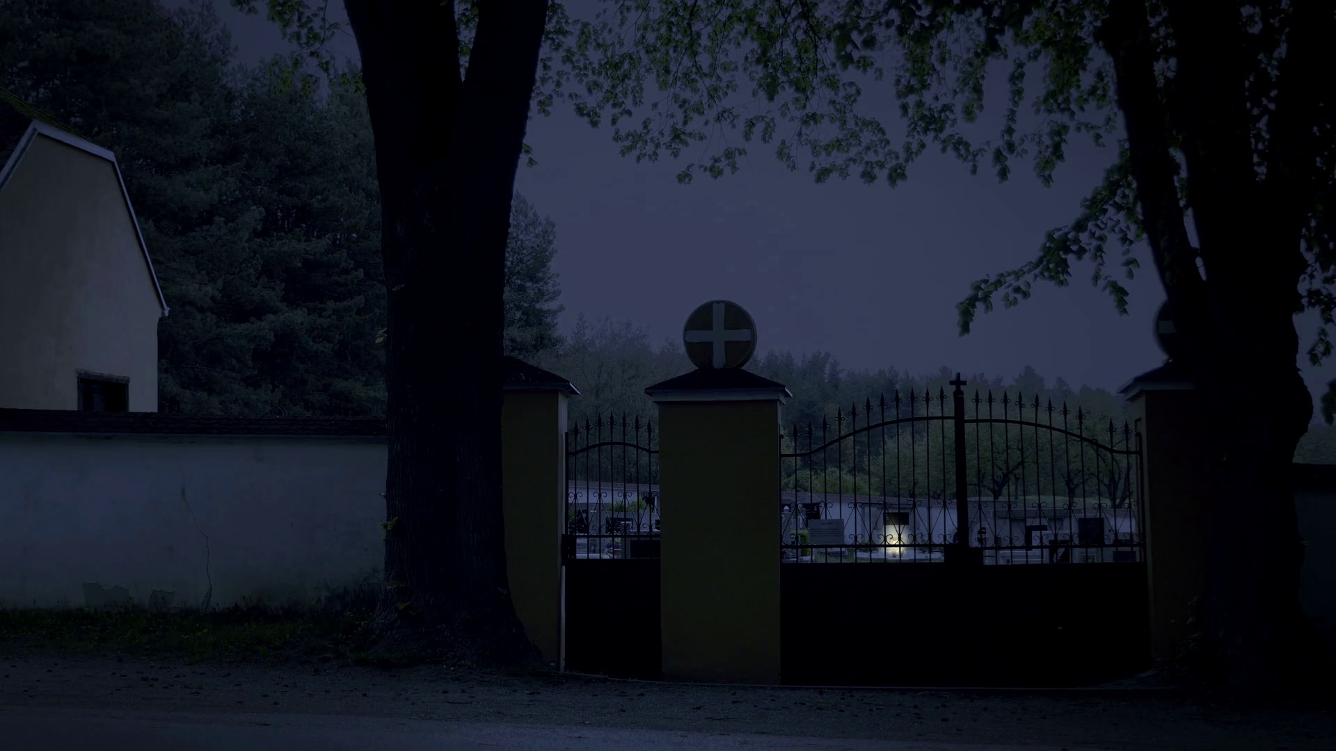 Scary cemetery at night. Invisible spirit closes and opens the gate ...