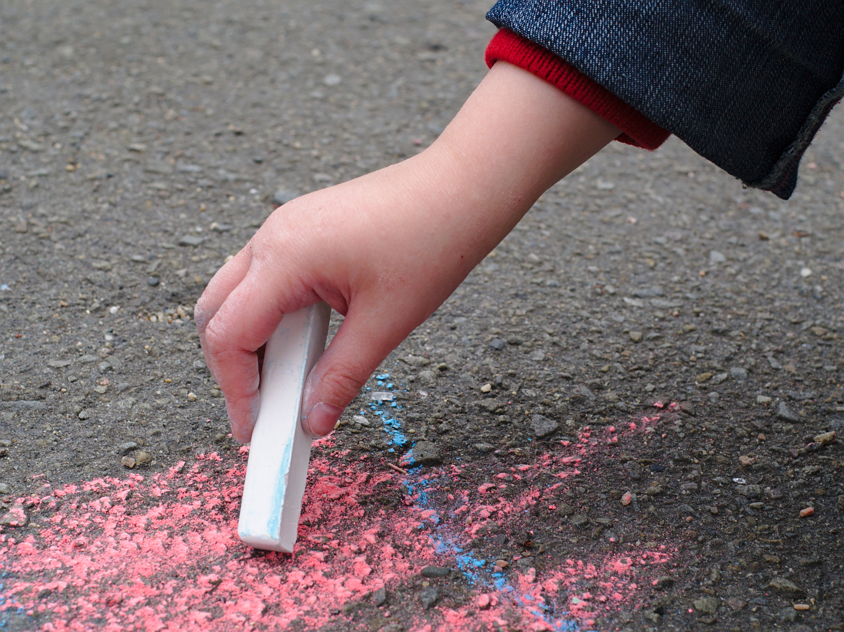 Child drawing with sidewalk chalk photo