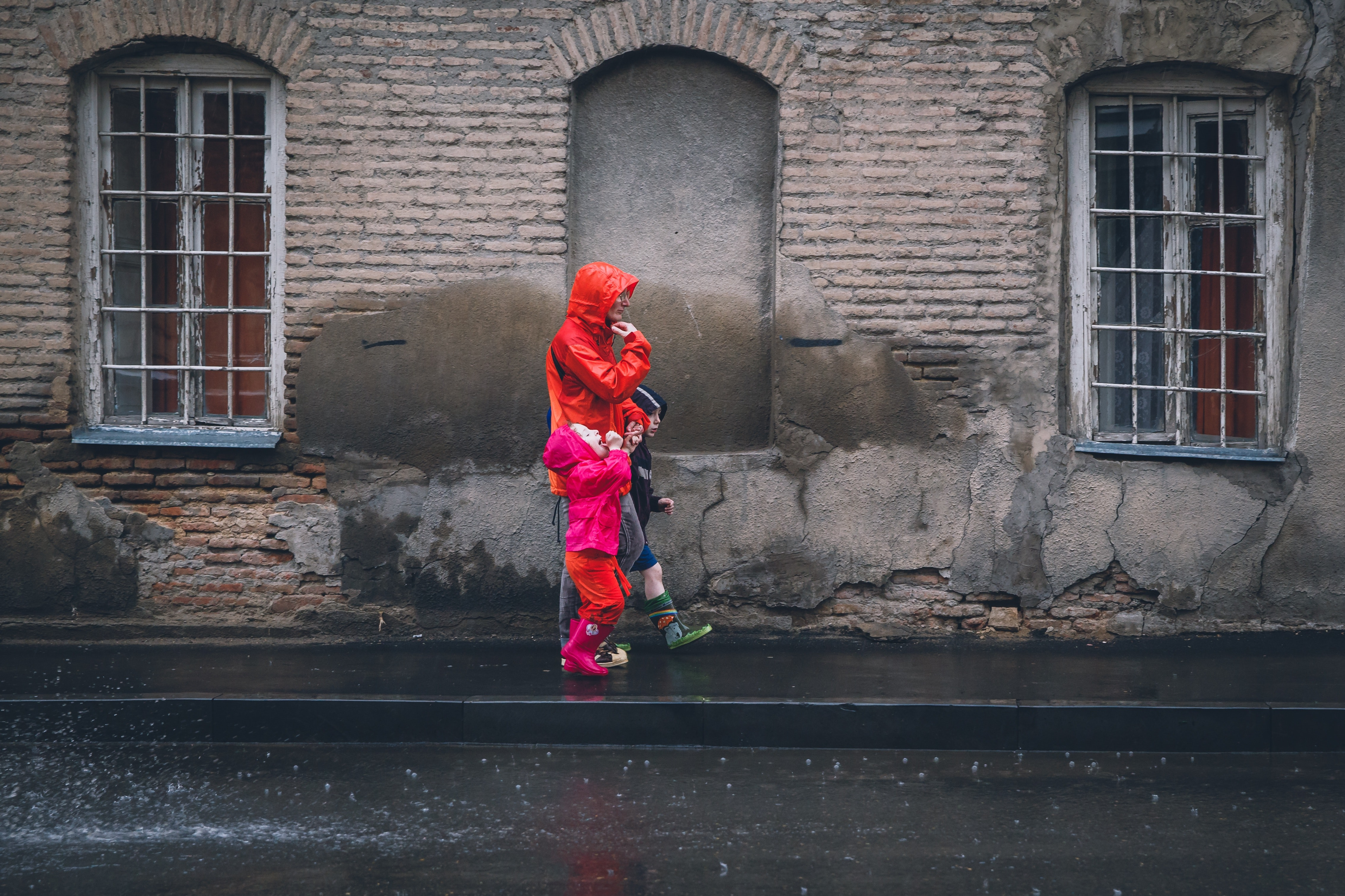 Children And Man Walking On A Sidewalk During Daytime Raincoat Street Wall