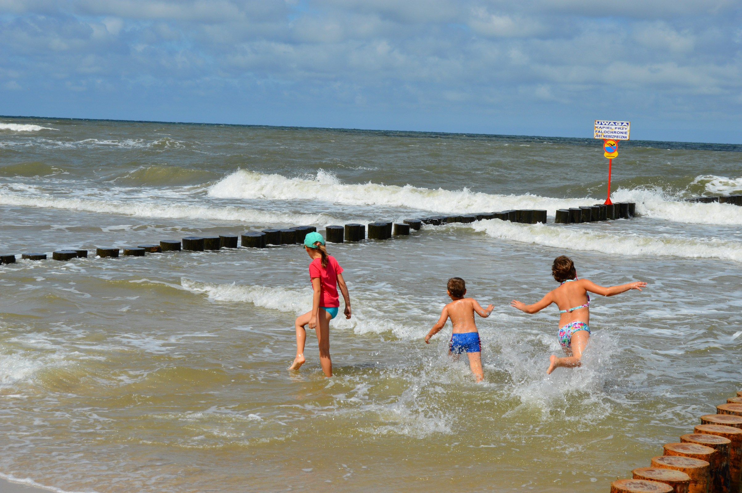 Children playing in a stormy sea near the breakwater. baltic sea photo
