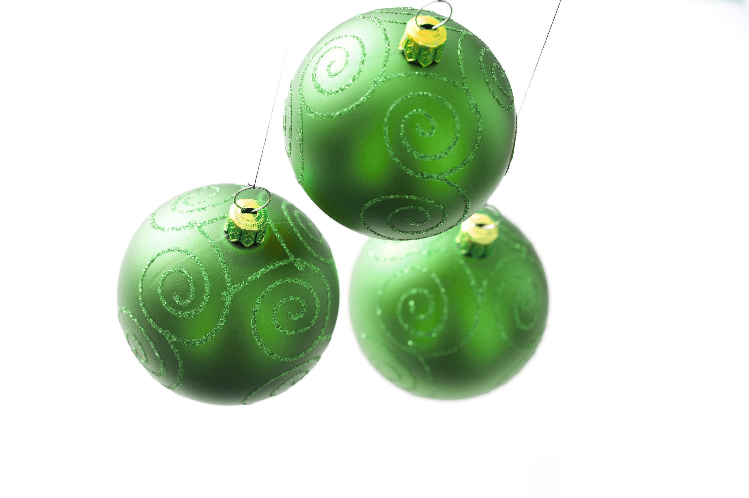 Photo of Three green Christmas balls hanging against of white ...