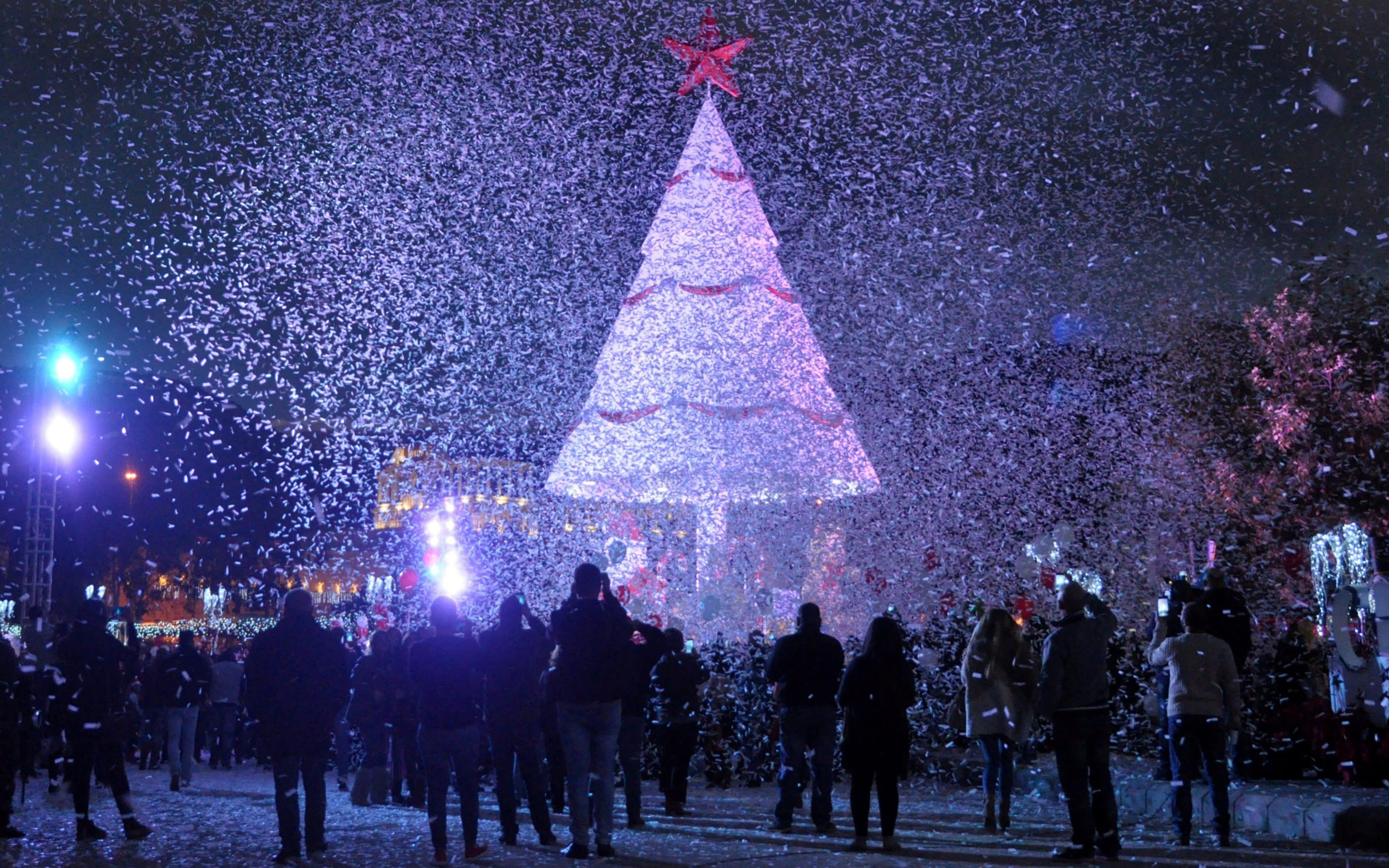 People gather under a Christmas Tree, marking the beginning of ...