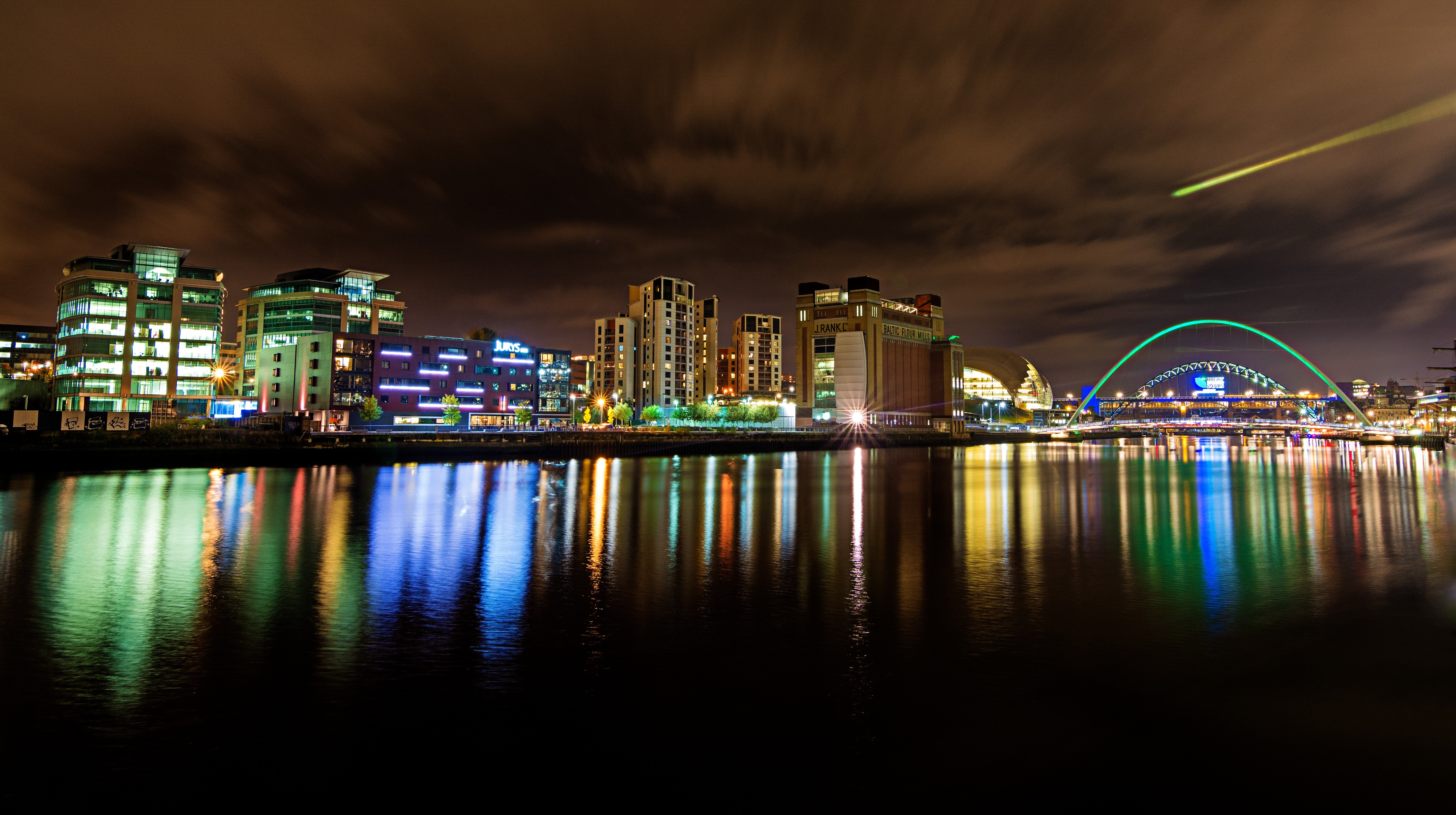 Cityscape at nighttime reflecting on body of water photo