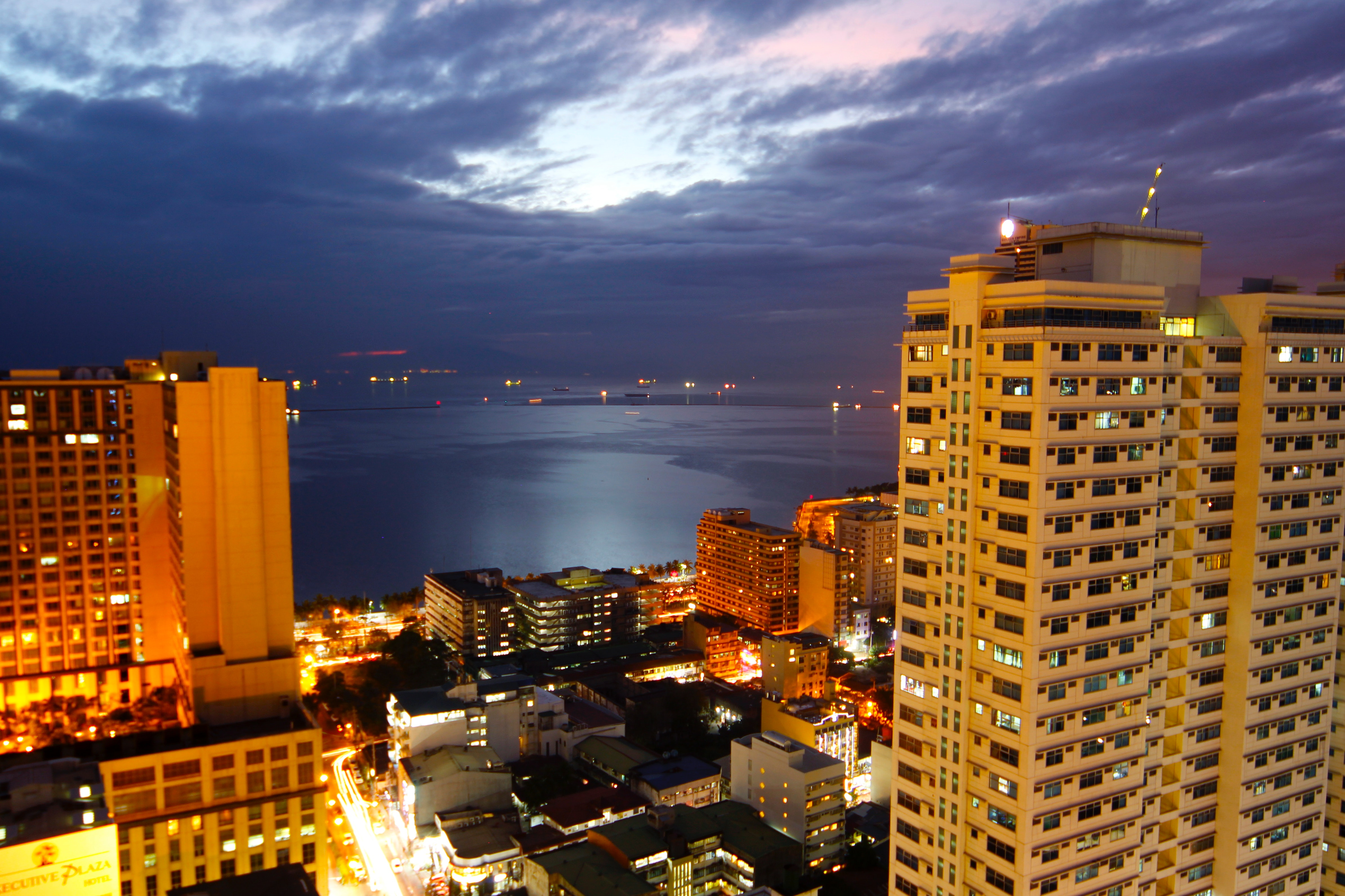 Cityscape lighted high-rise buildings beside calm body of water photo