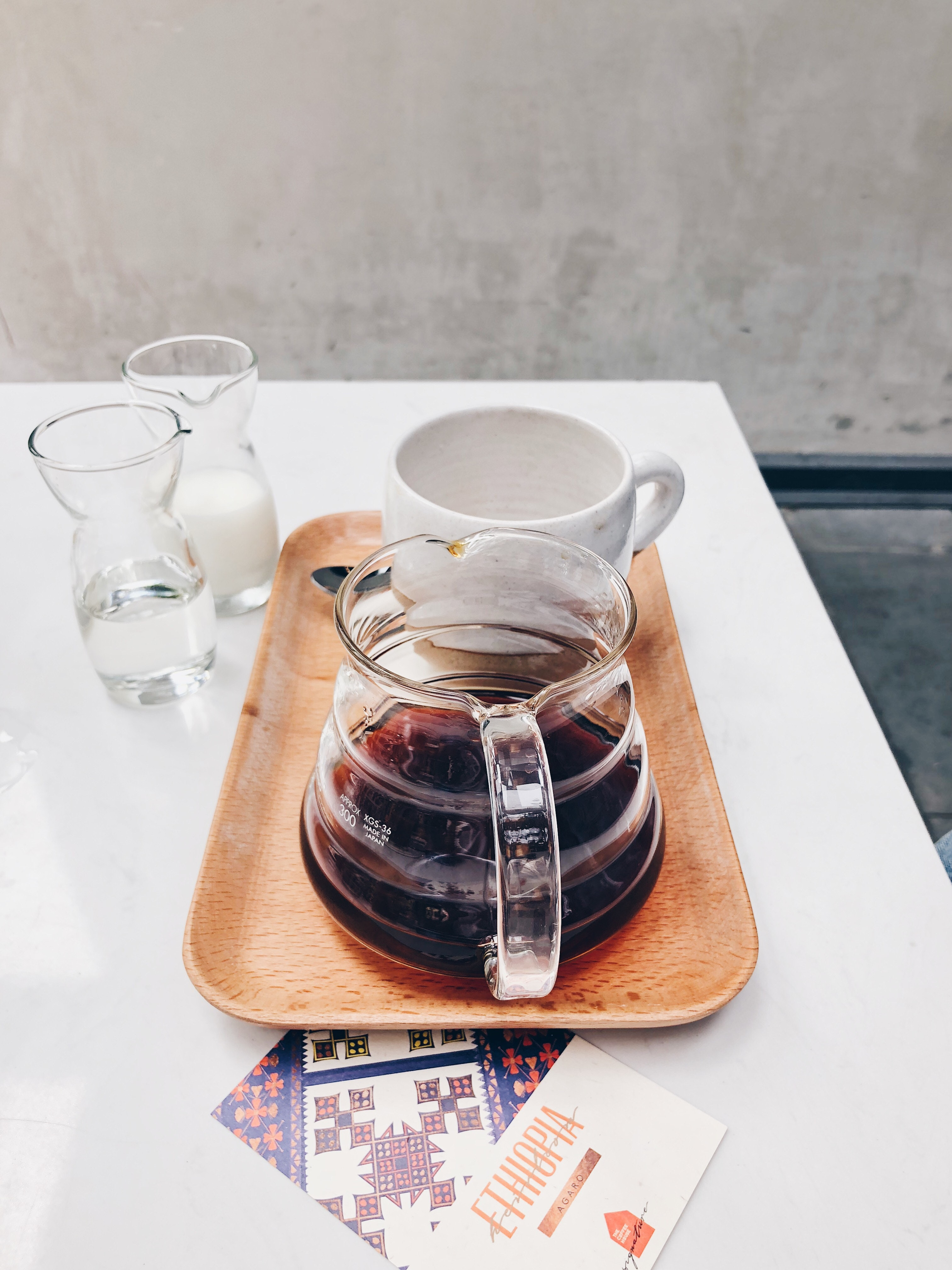 Clear glass coffee pot near white mug on brown tray photo