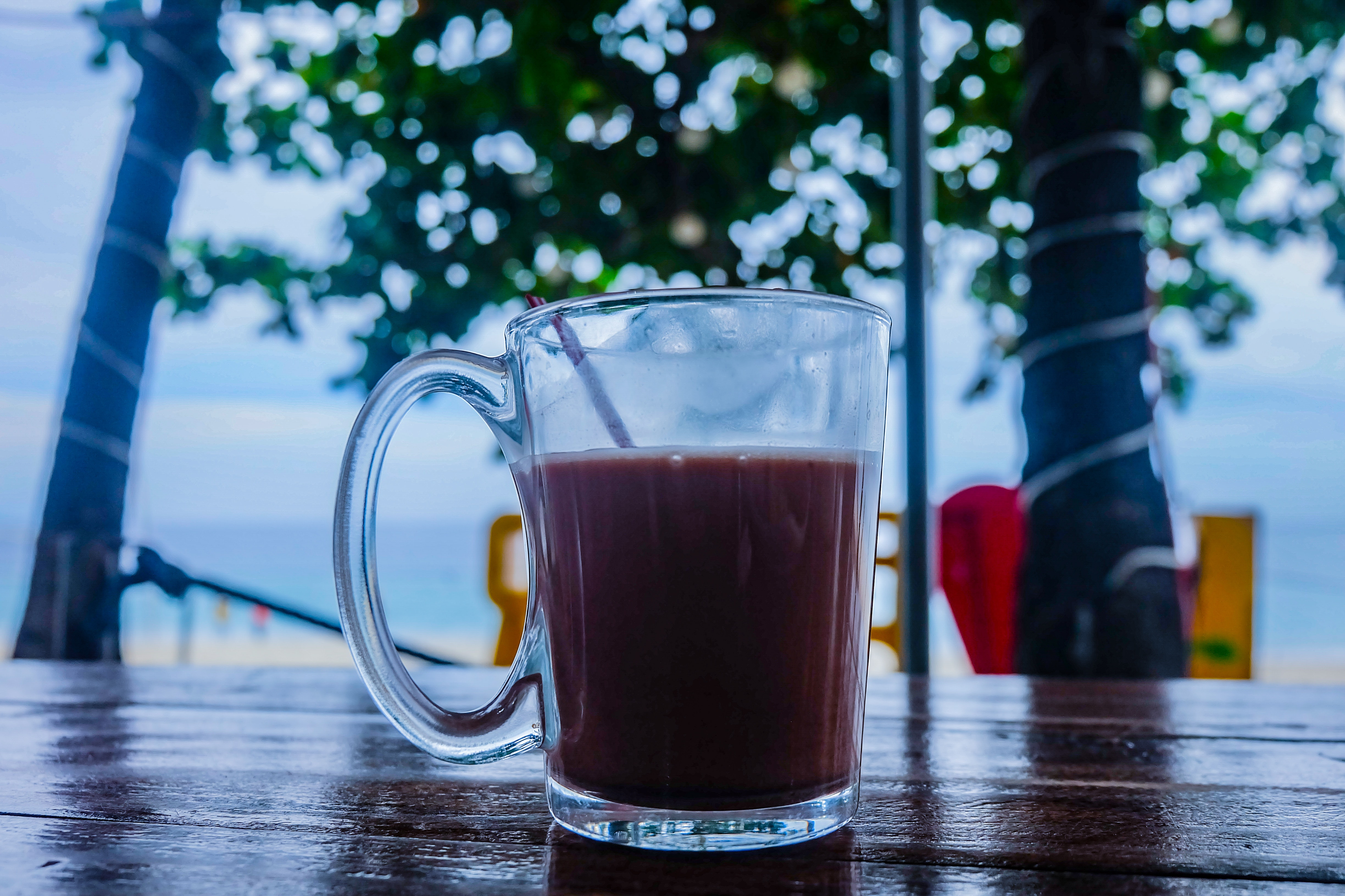 Clear glass mug with beverage on brown wooden table photo