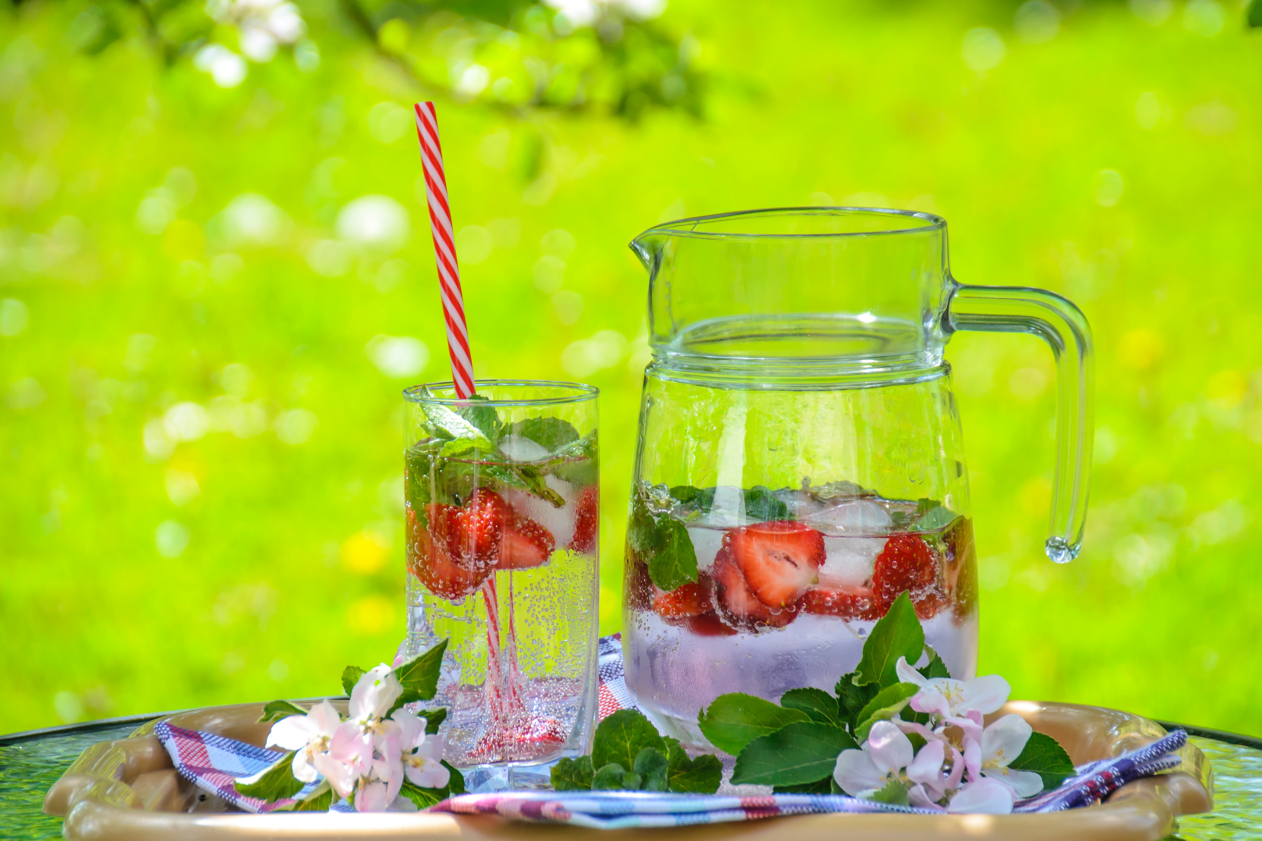 Clear glass pitcher with water and strawberry photo