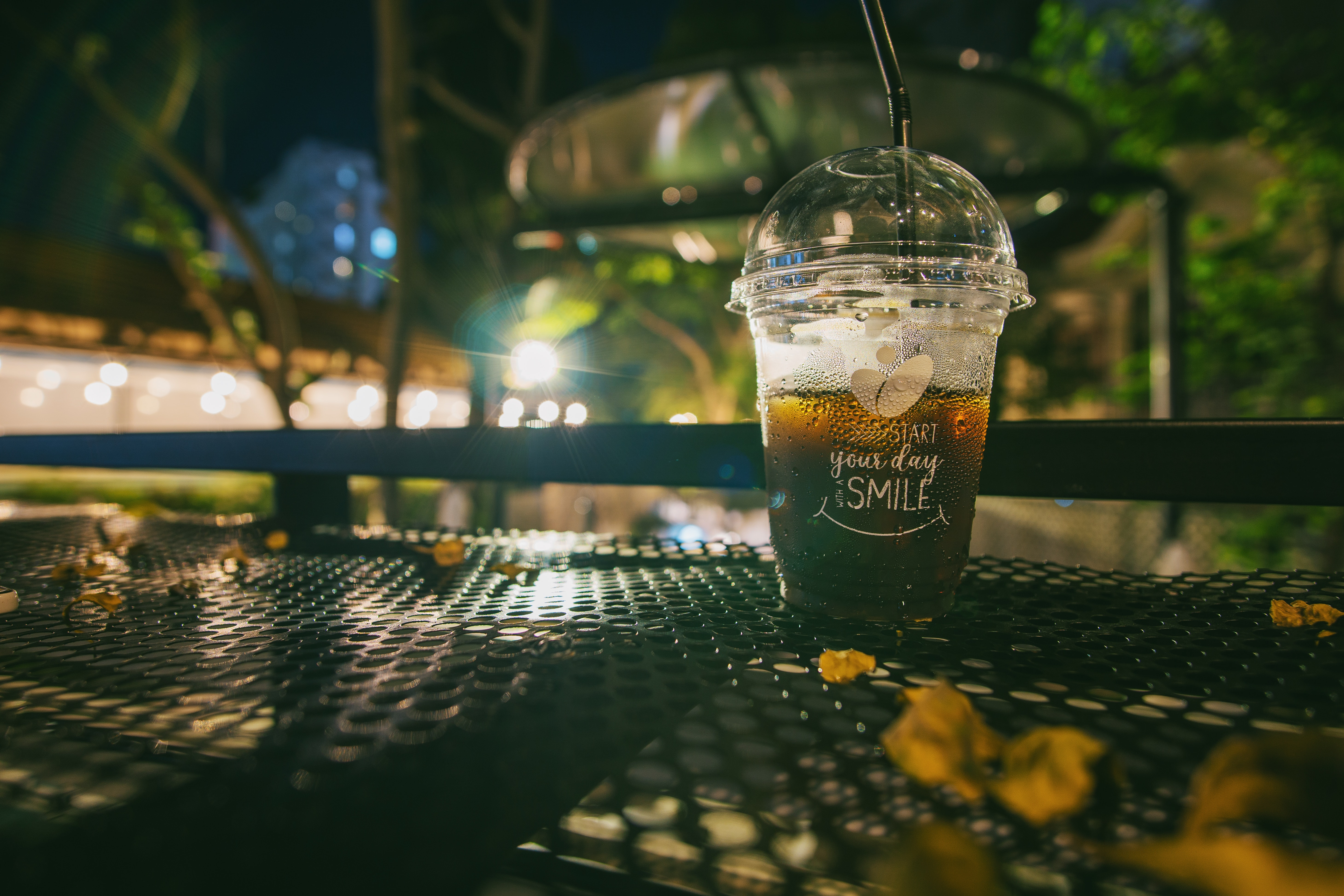 Clear plastic disposable cup with straw half-filled with juice on metal table photo
