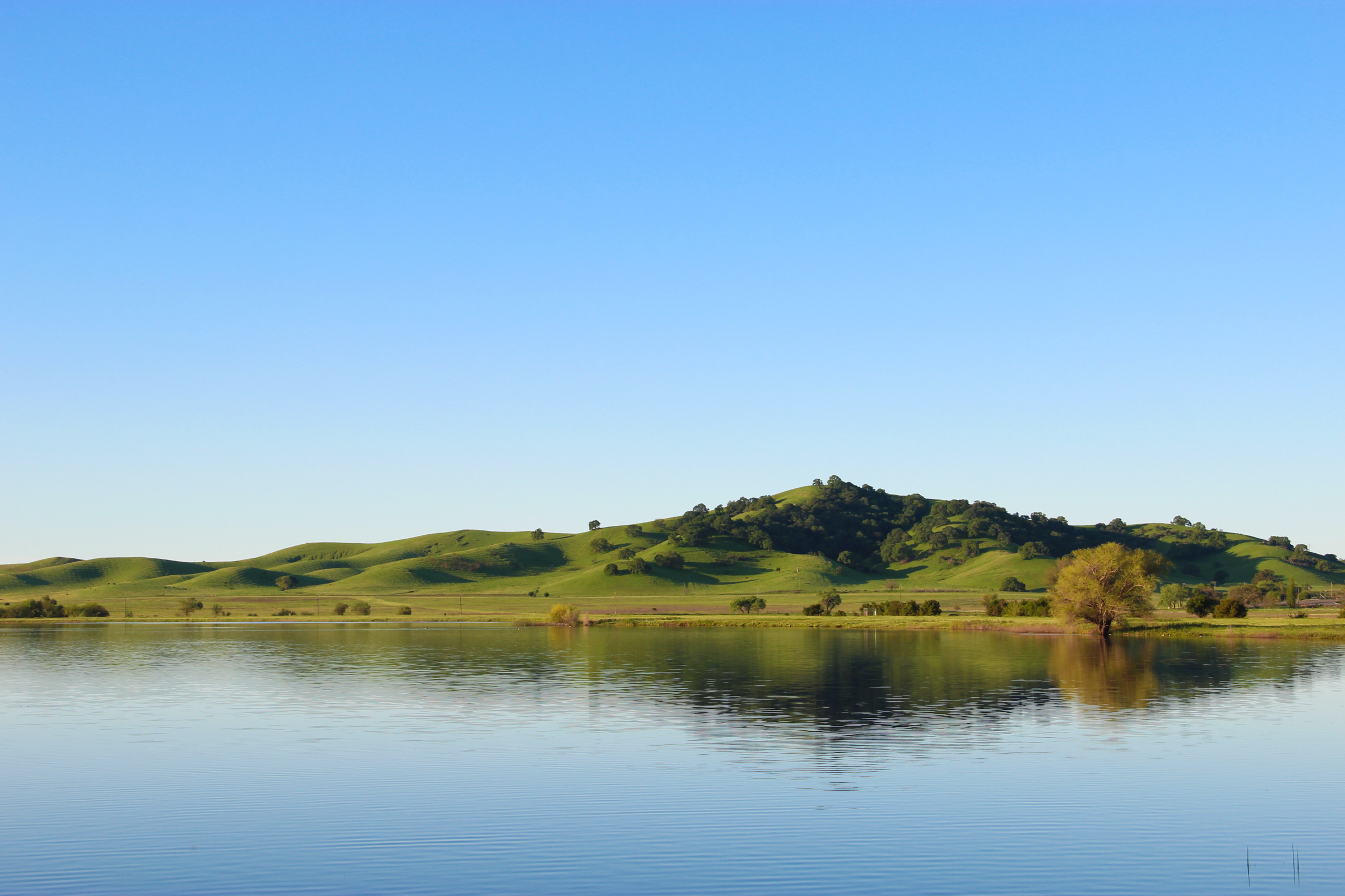Free Stock Photo of Hill by Still Lake Under Clear Sky