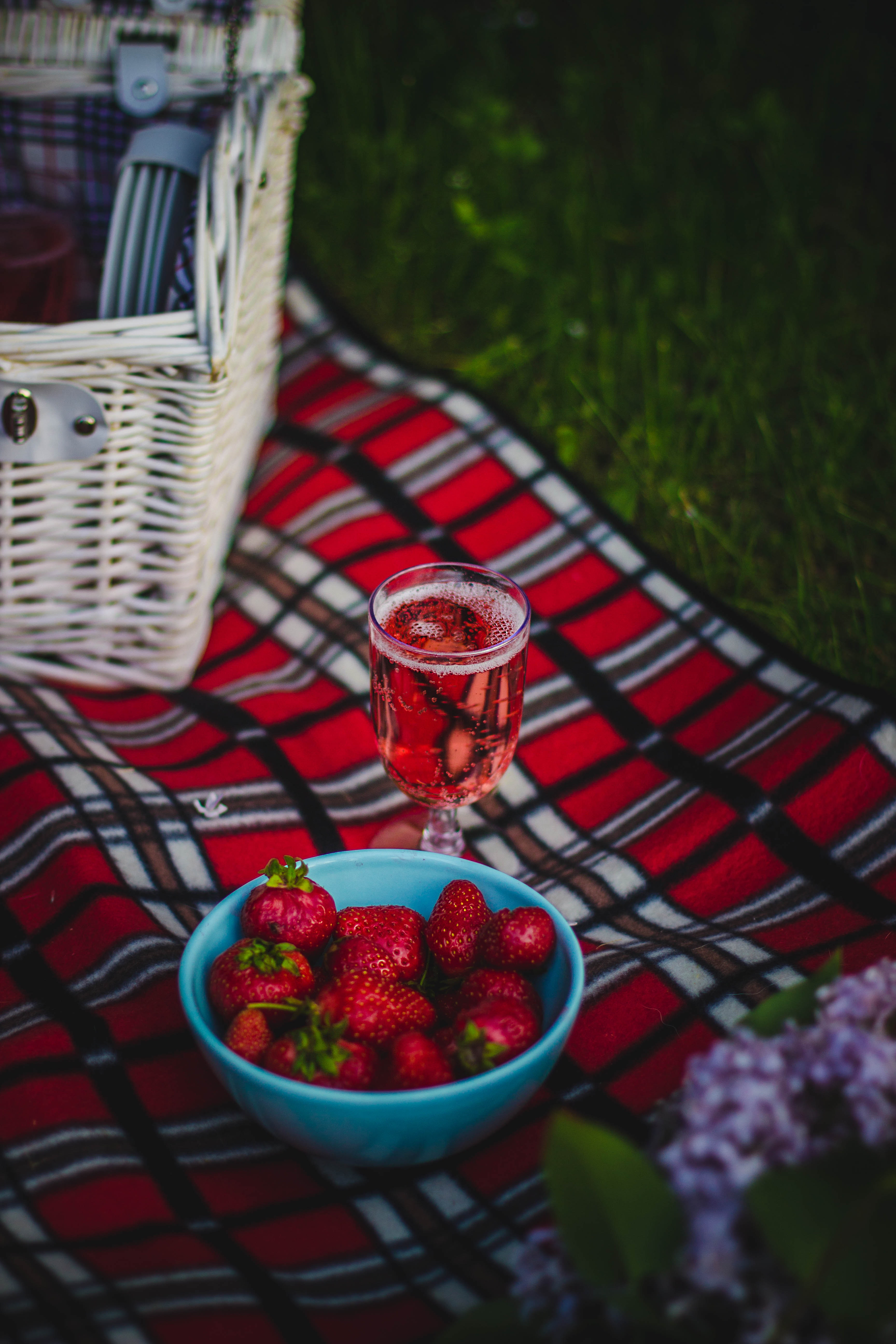 Clear wine glass with wine near strawberry fruit on red white and black plaid textile photo