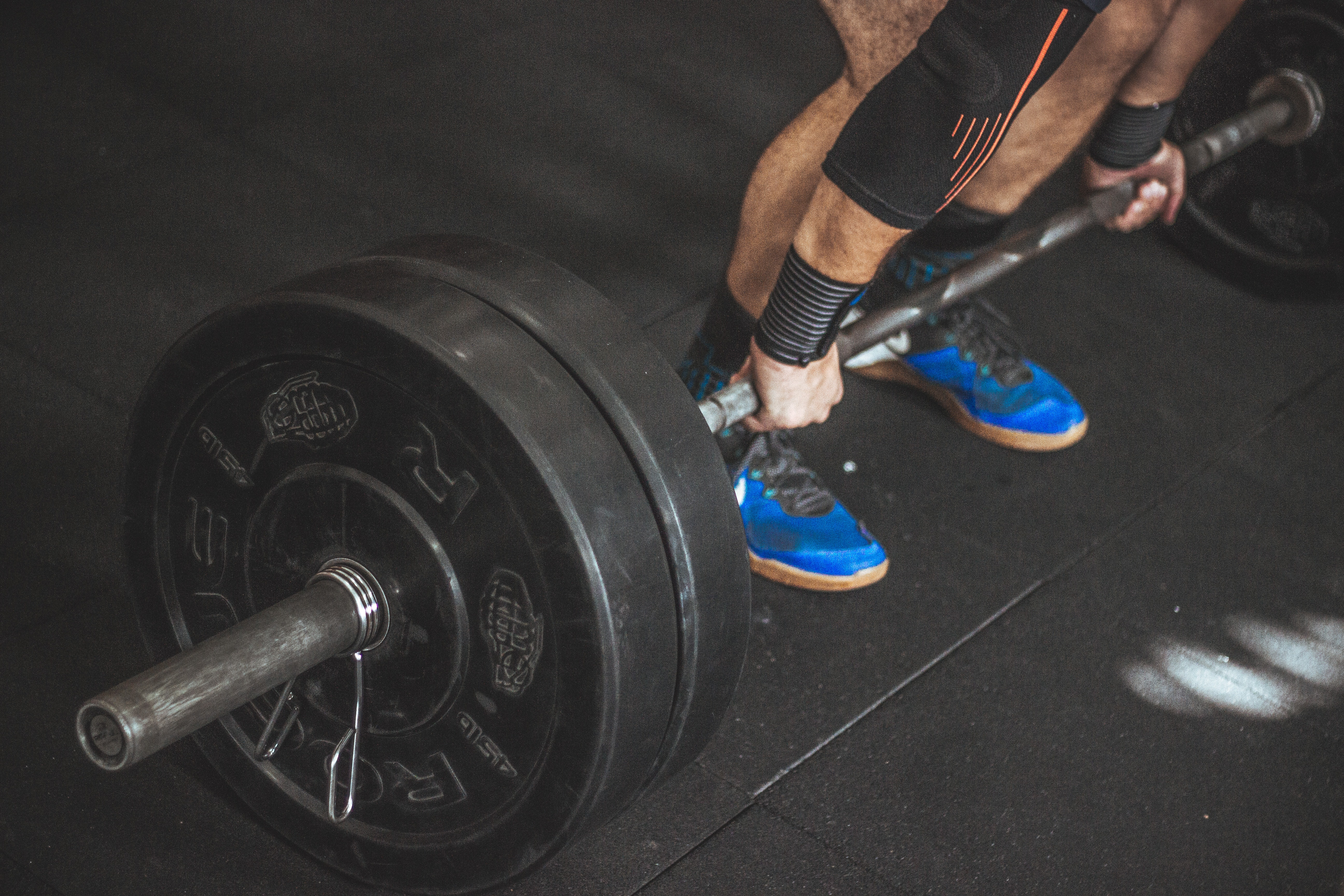 Close-up of a person's lower body holding barbell photo