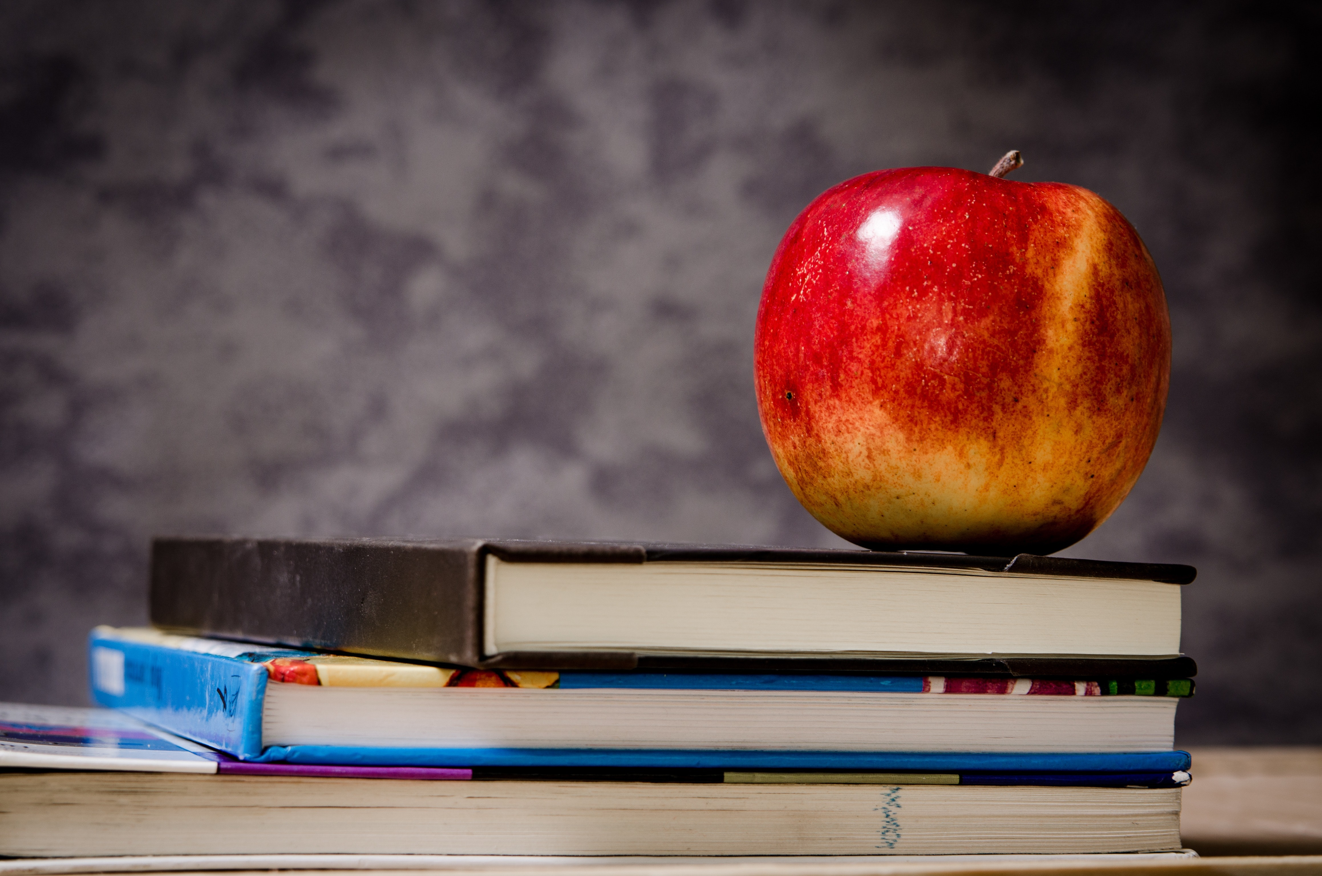 Close-up of apple on top of books photo