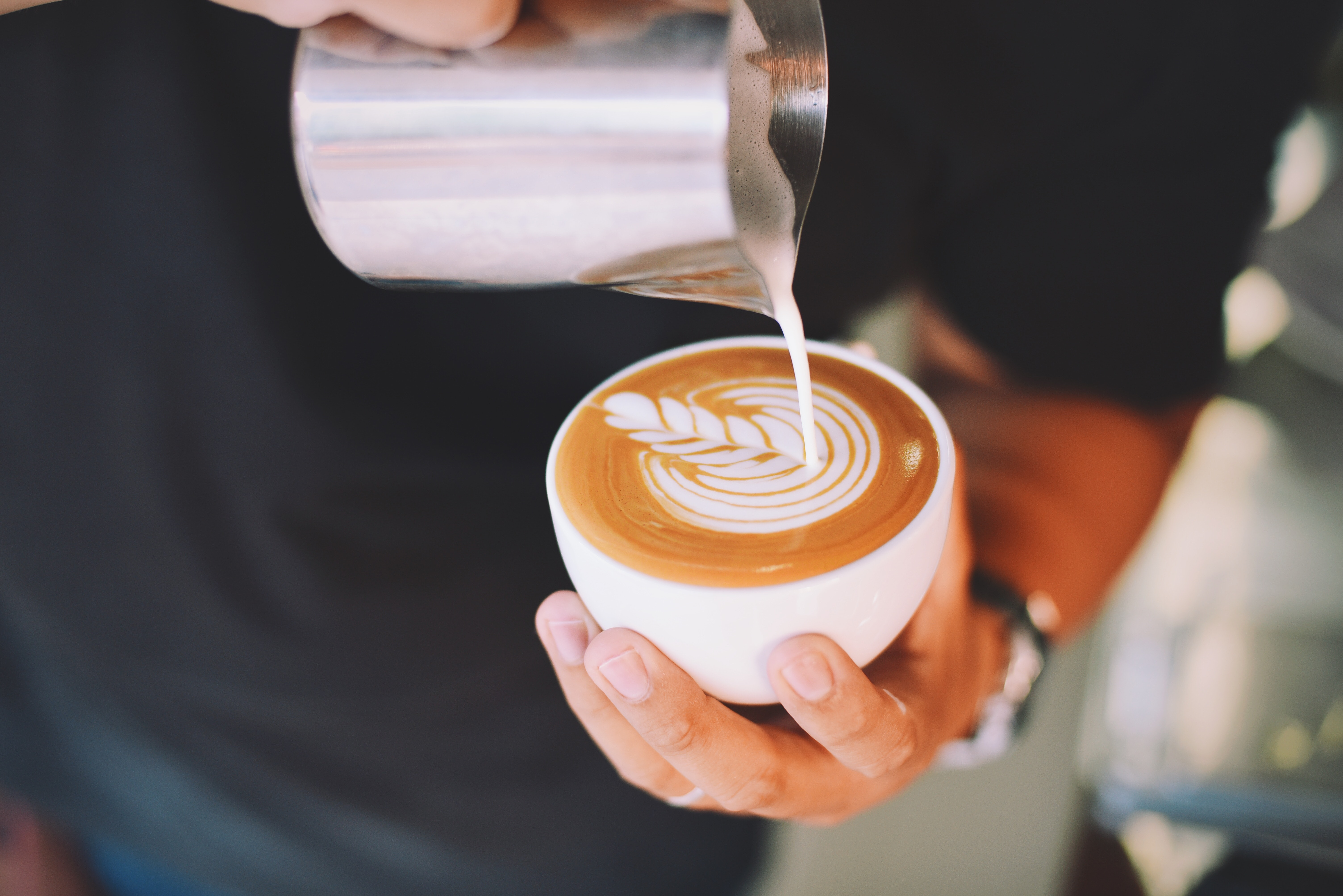 Close-up of hand holding cappuccino photo
