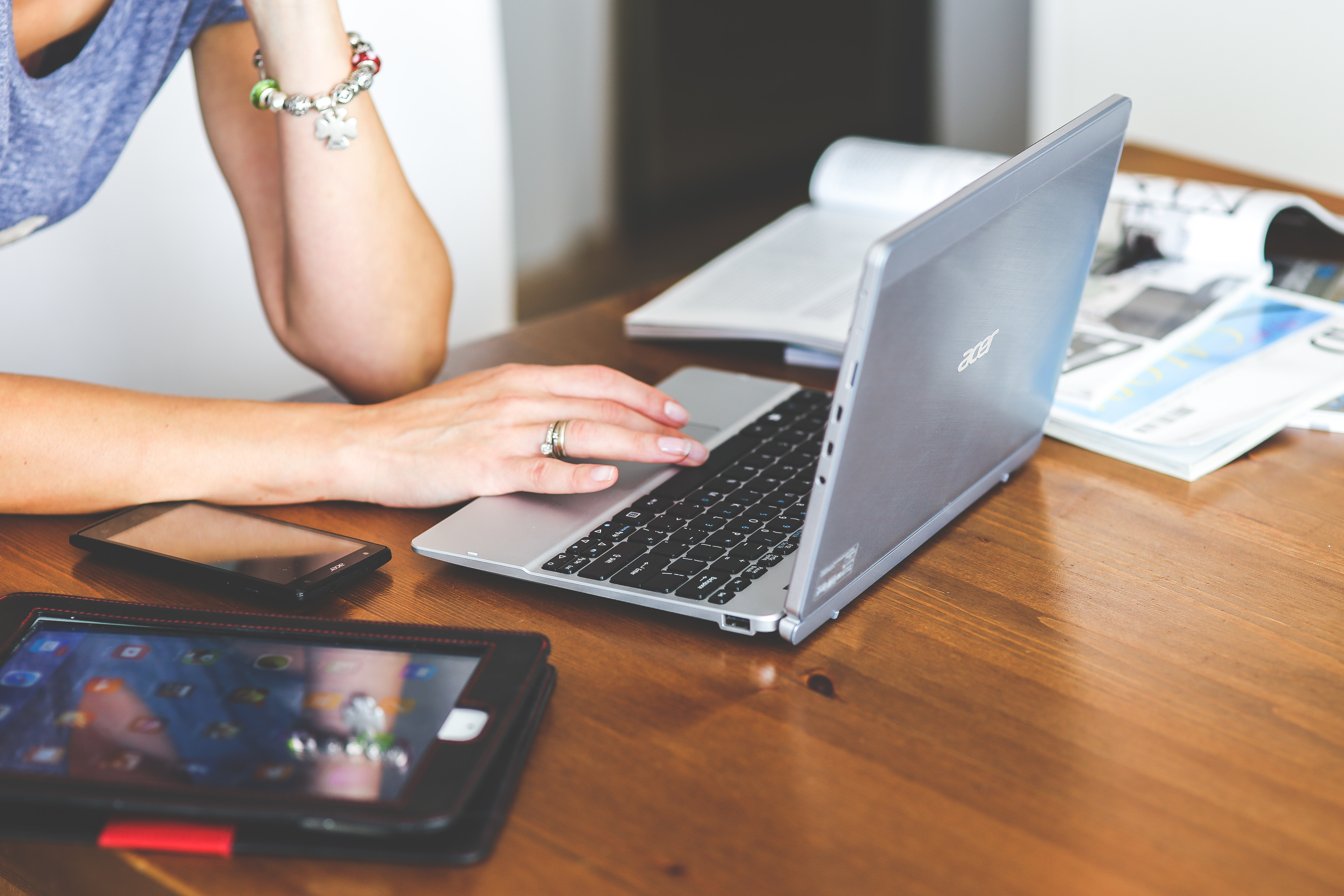 Close-up of woman typing on keyboard of laptop photo