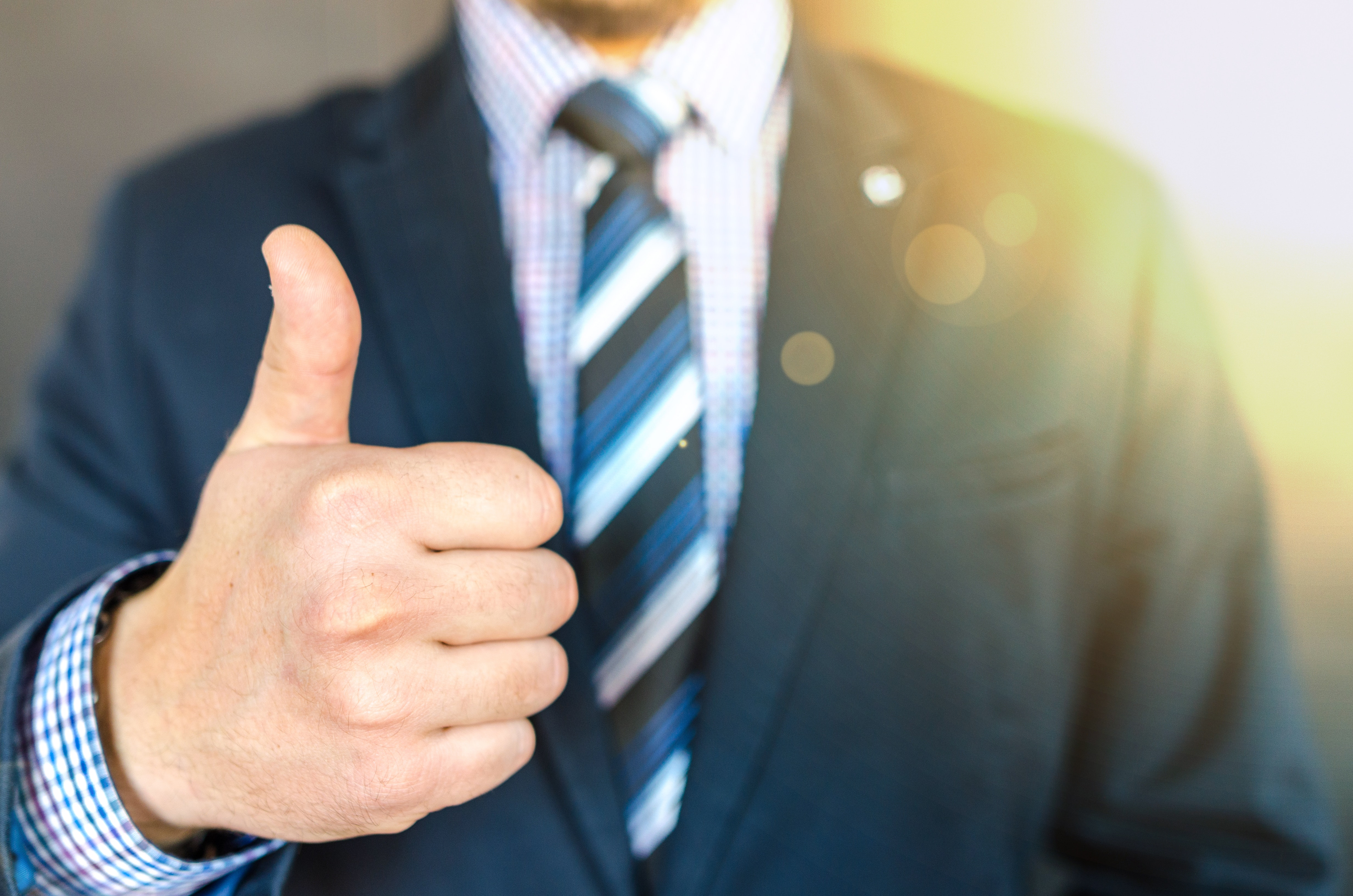 Close-up photo of man wearing black suit jacket doing thumbs up gesture