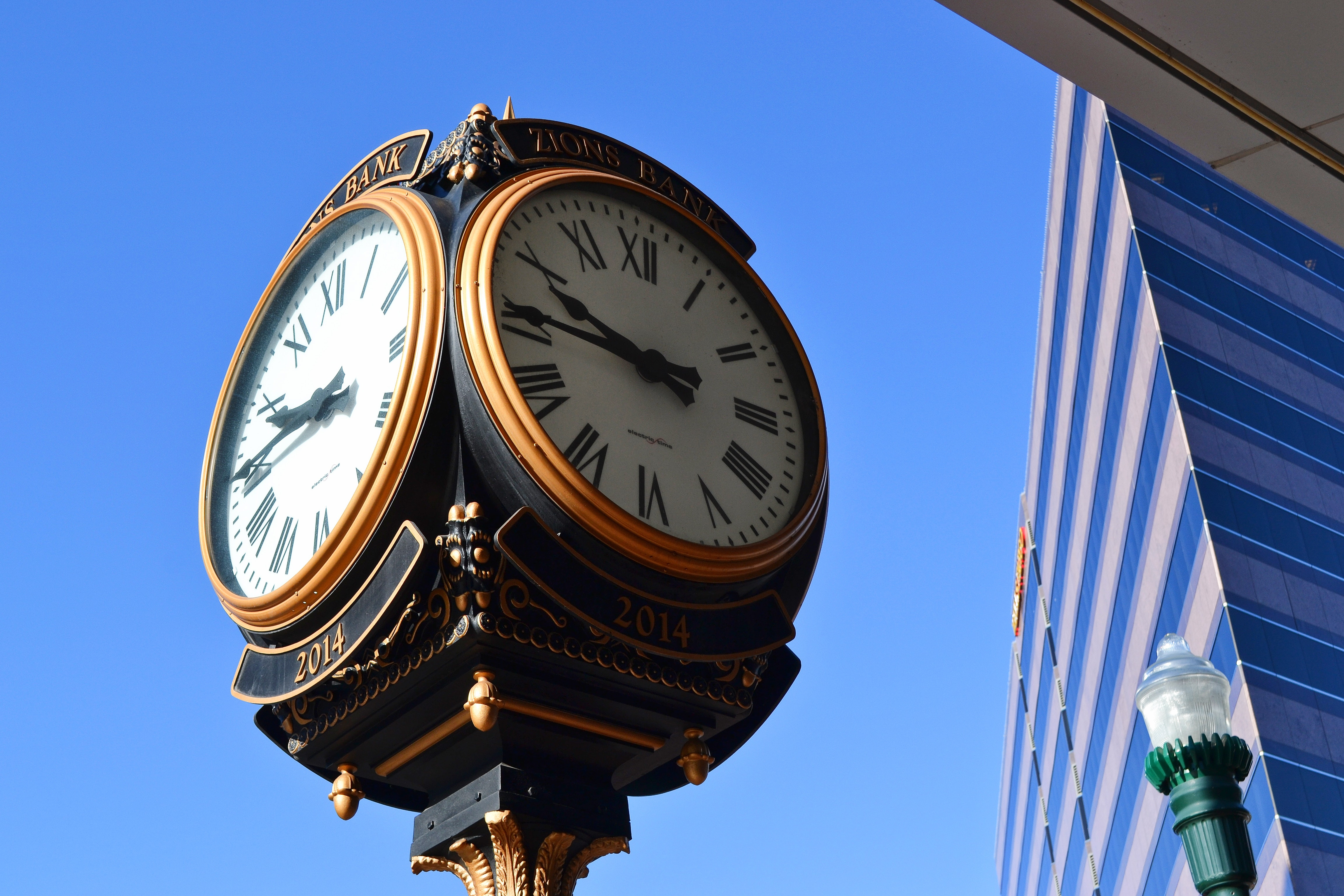 Old forged street clock under a bright blue sky photo