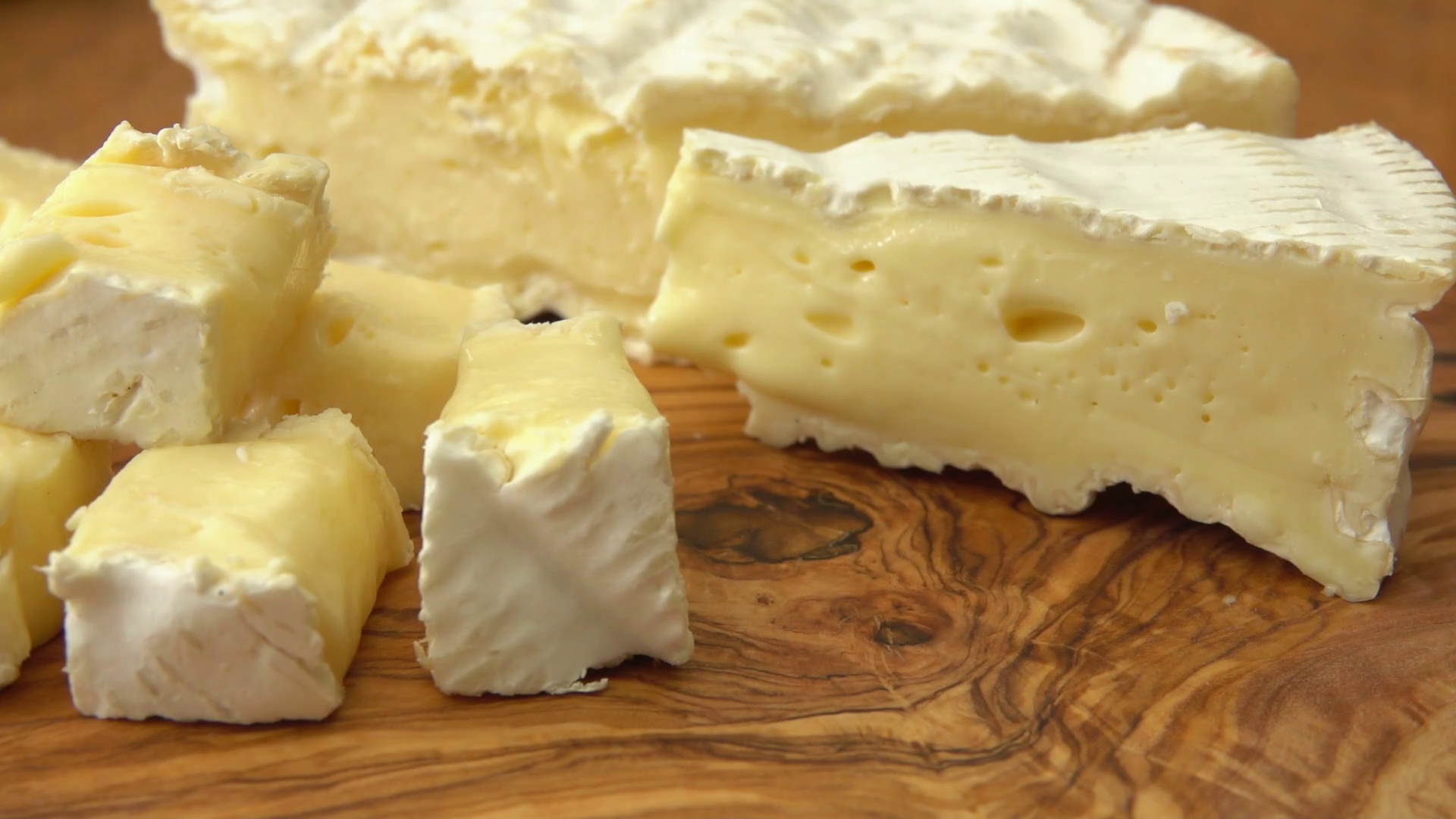 Close up Soft brie cheese cubes on rustic wooden board. Pan movement ...