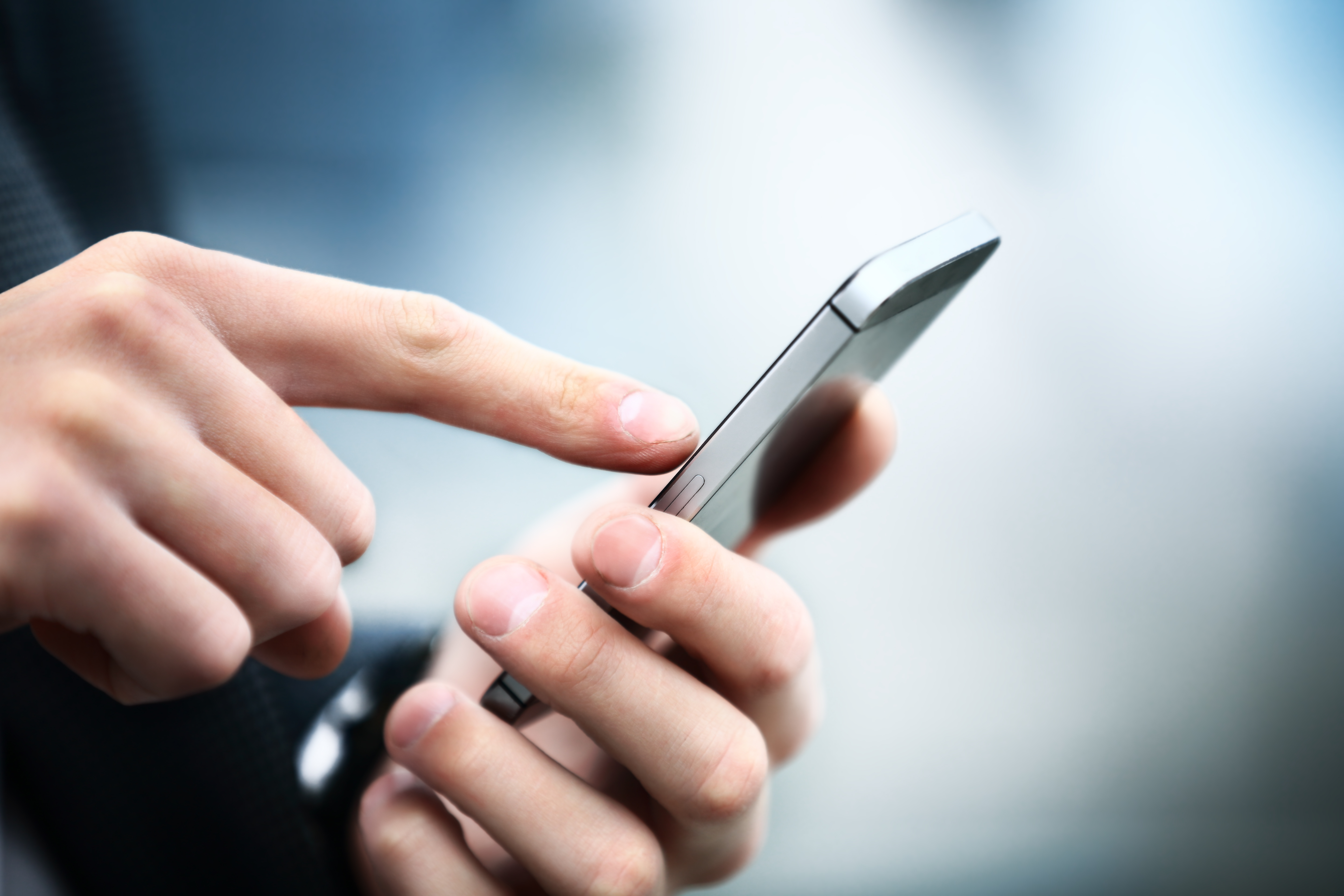 Close up of a man using mobile smart phone |