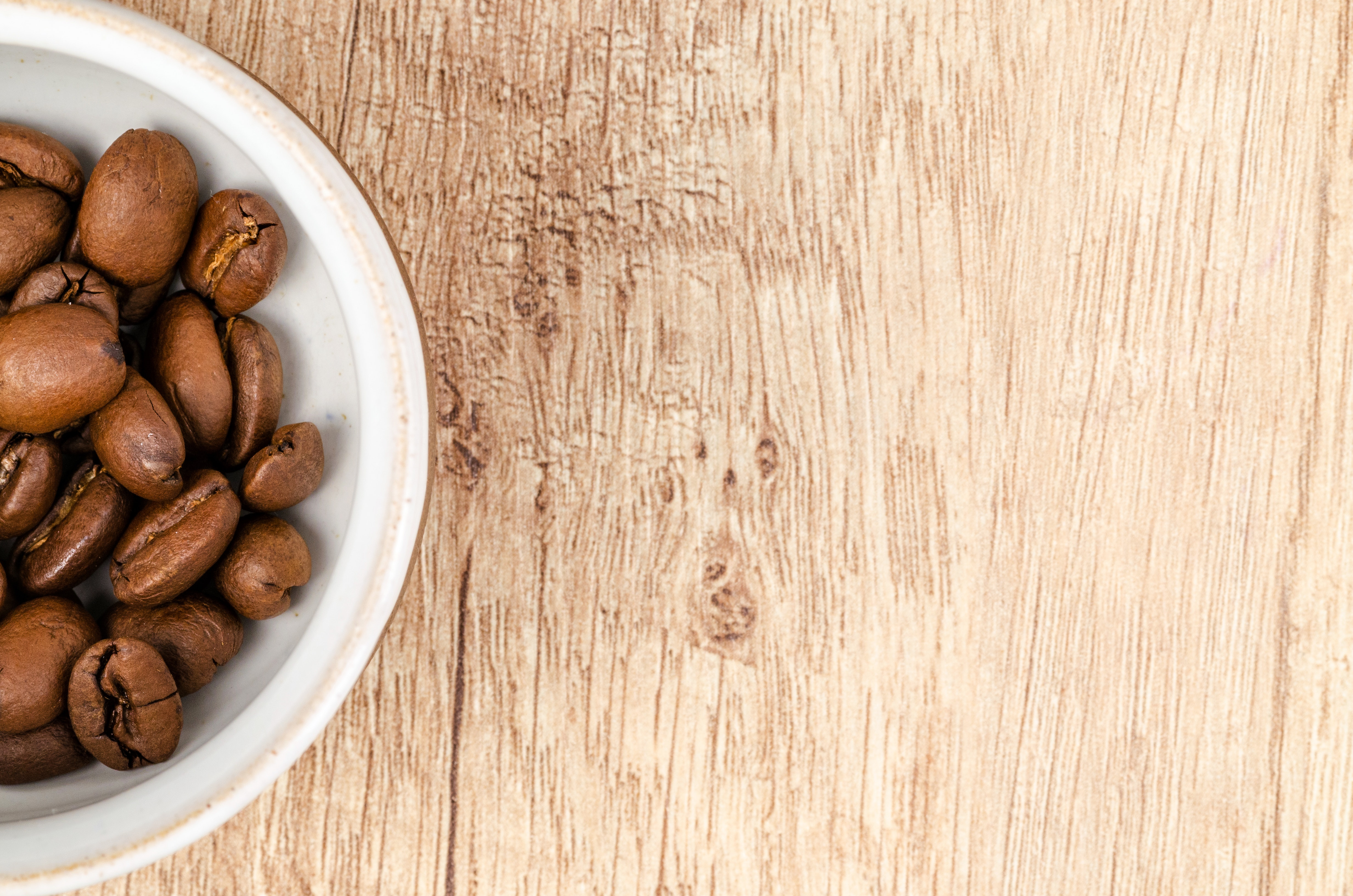 Coffee beans on white ceramic bowl on top of brown wooden surface photo