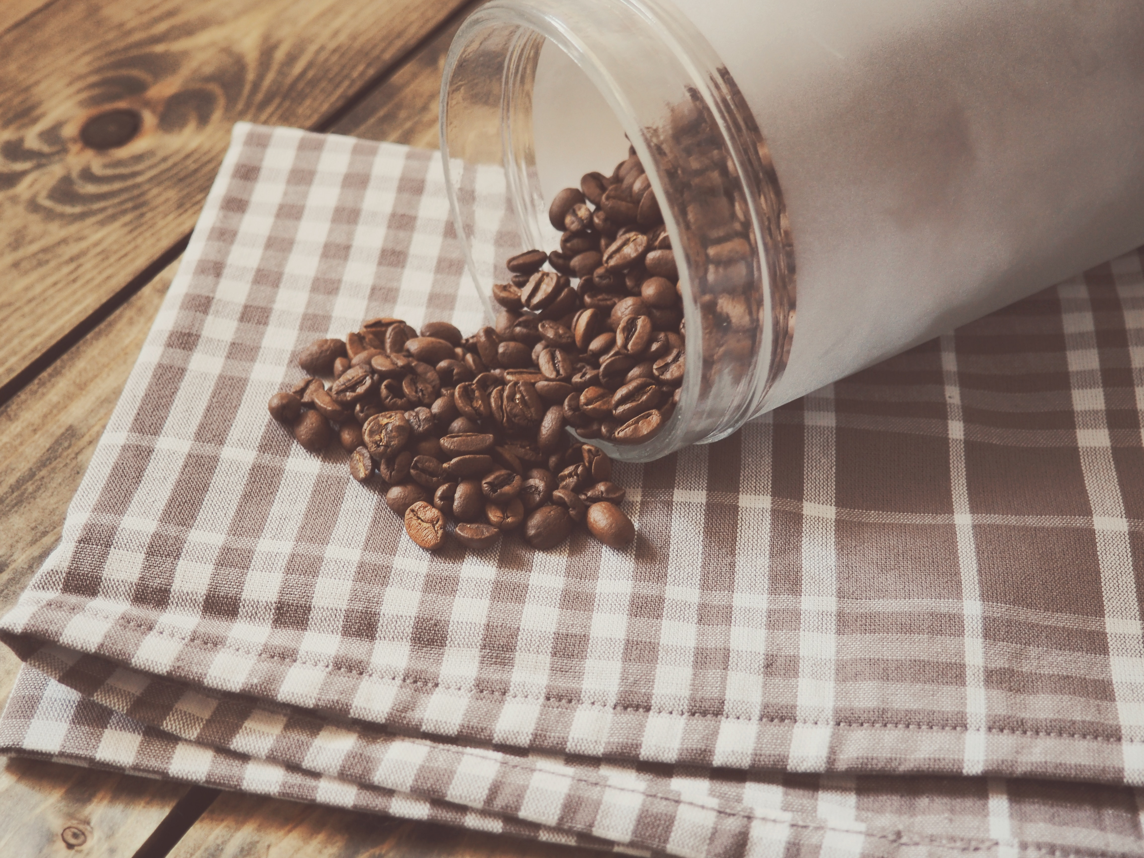 Coffee beans spilled on gray and white plaid textile photo