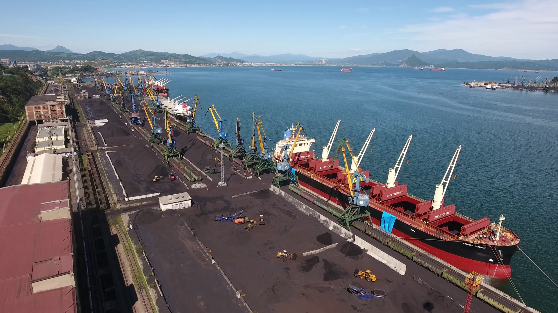 Aerial drone flight over large black coal commercial industrial port ...