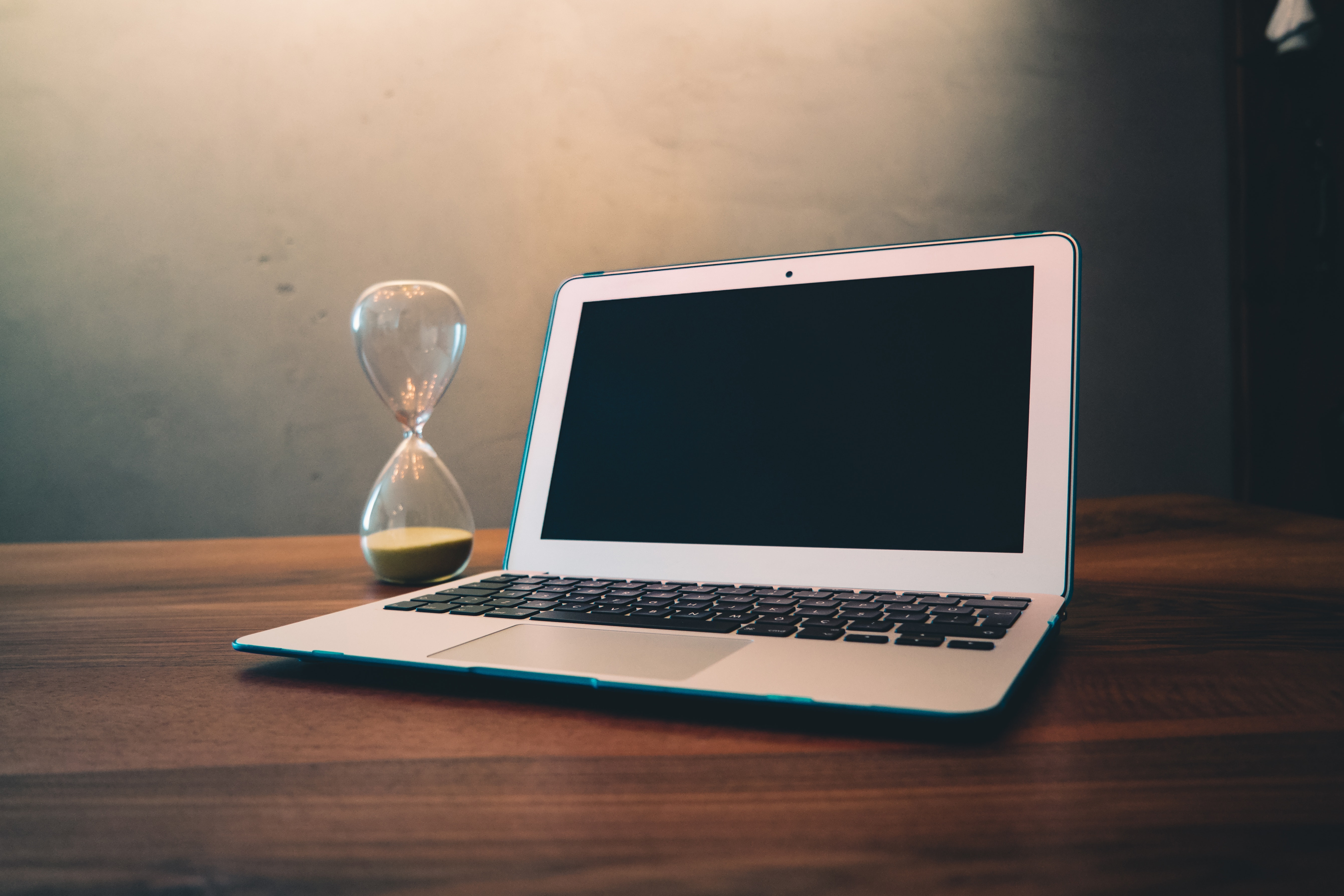 Computer laptop beside hour glass on brown wooden surface photo