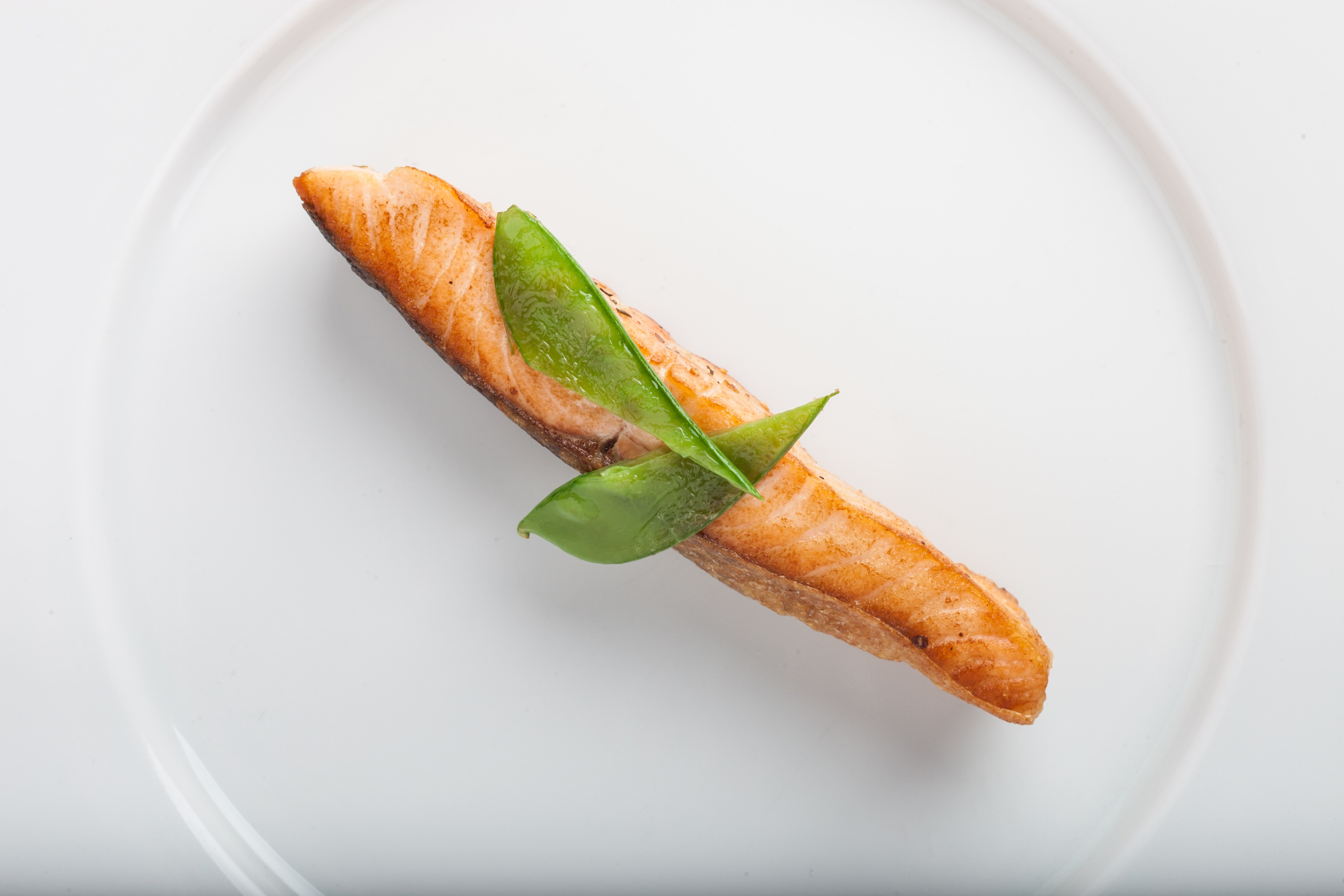 Cooked fish with two green leaf on round white ceramic plate photo