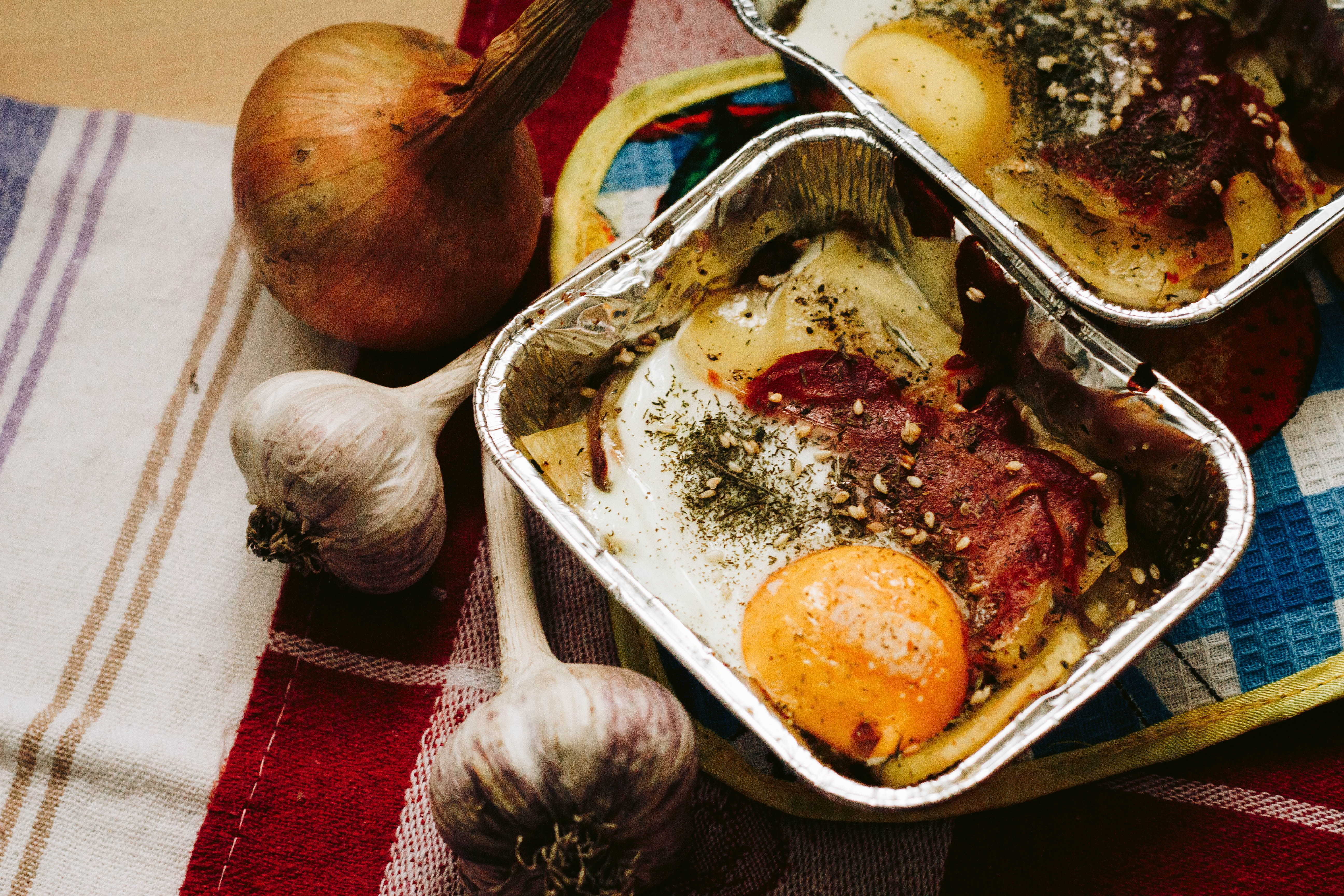 Cooked food in square grey tray beside garlics and onion photo