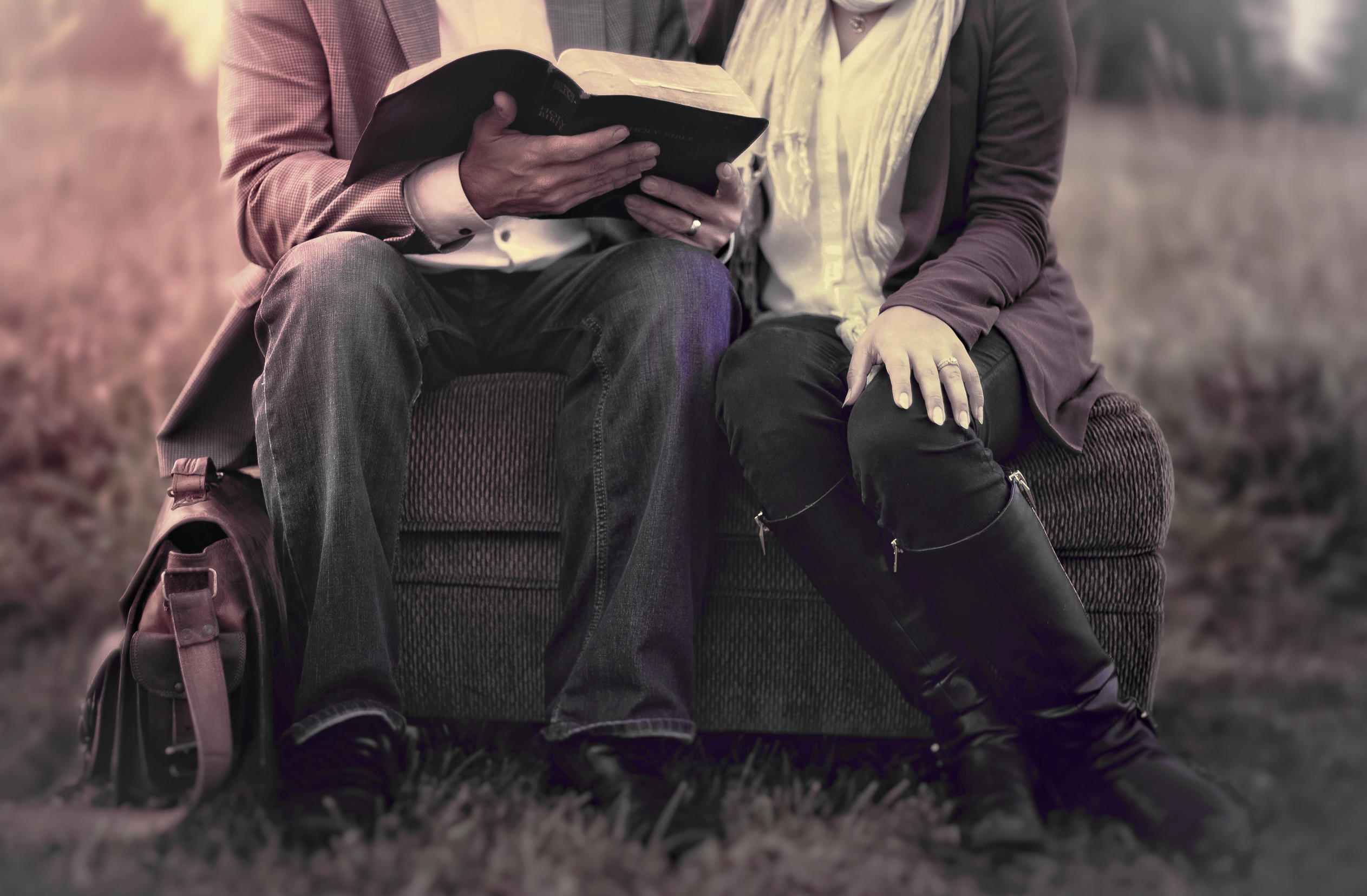 Couple in love reading outdoors - washed-out effect photo