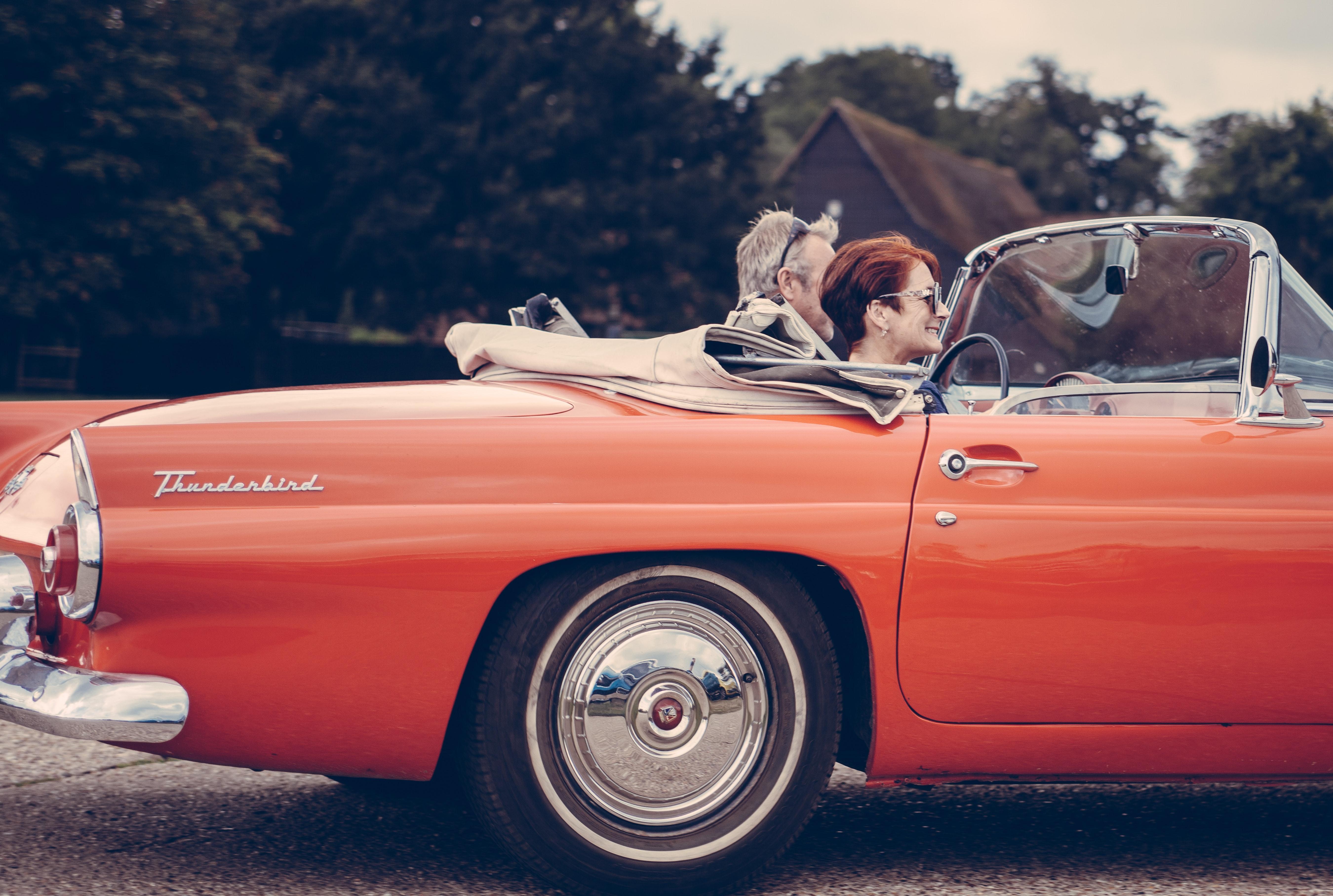 Couple Riding Red Ford Thunderbird during Daytime, Asphalt, Reflection, Vintage car, Vintage, HQ Photo