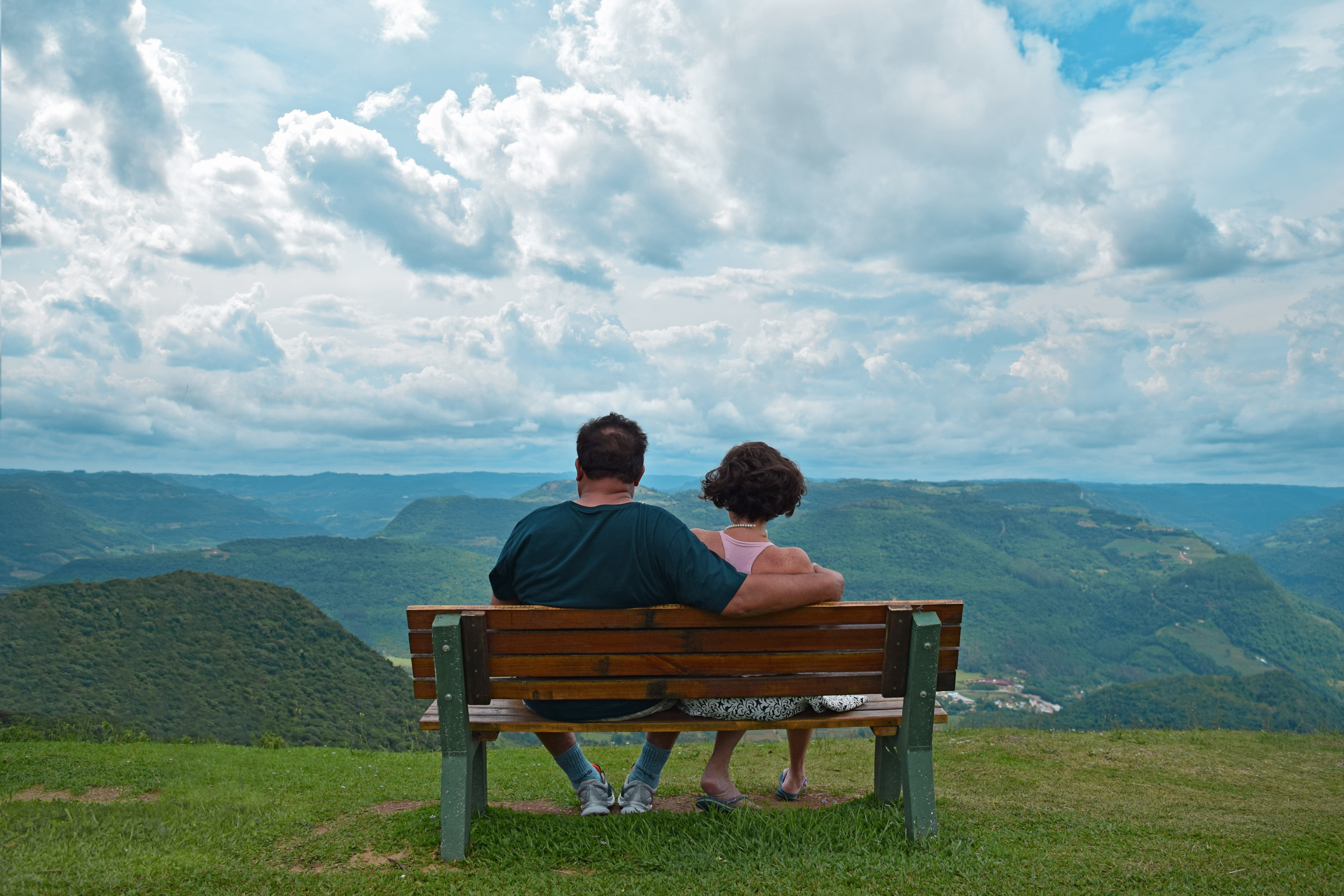 Couple sitting on brown wooden bench near mountains covered with grasses under blue cloudy sky photo