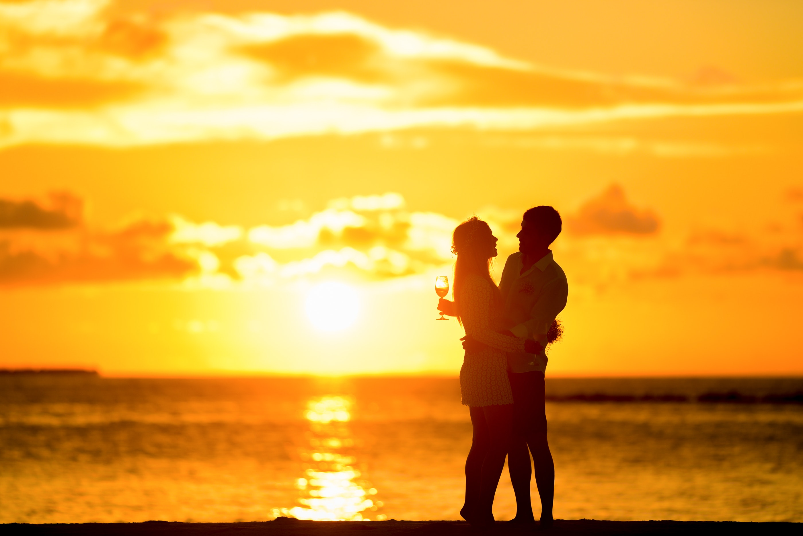 Couple standing in the seashore hugging each other during sunset photo