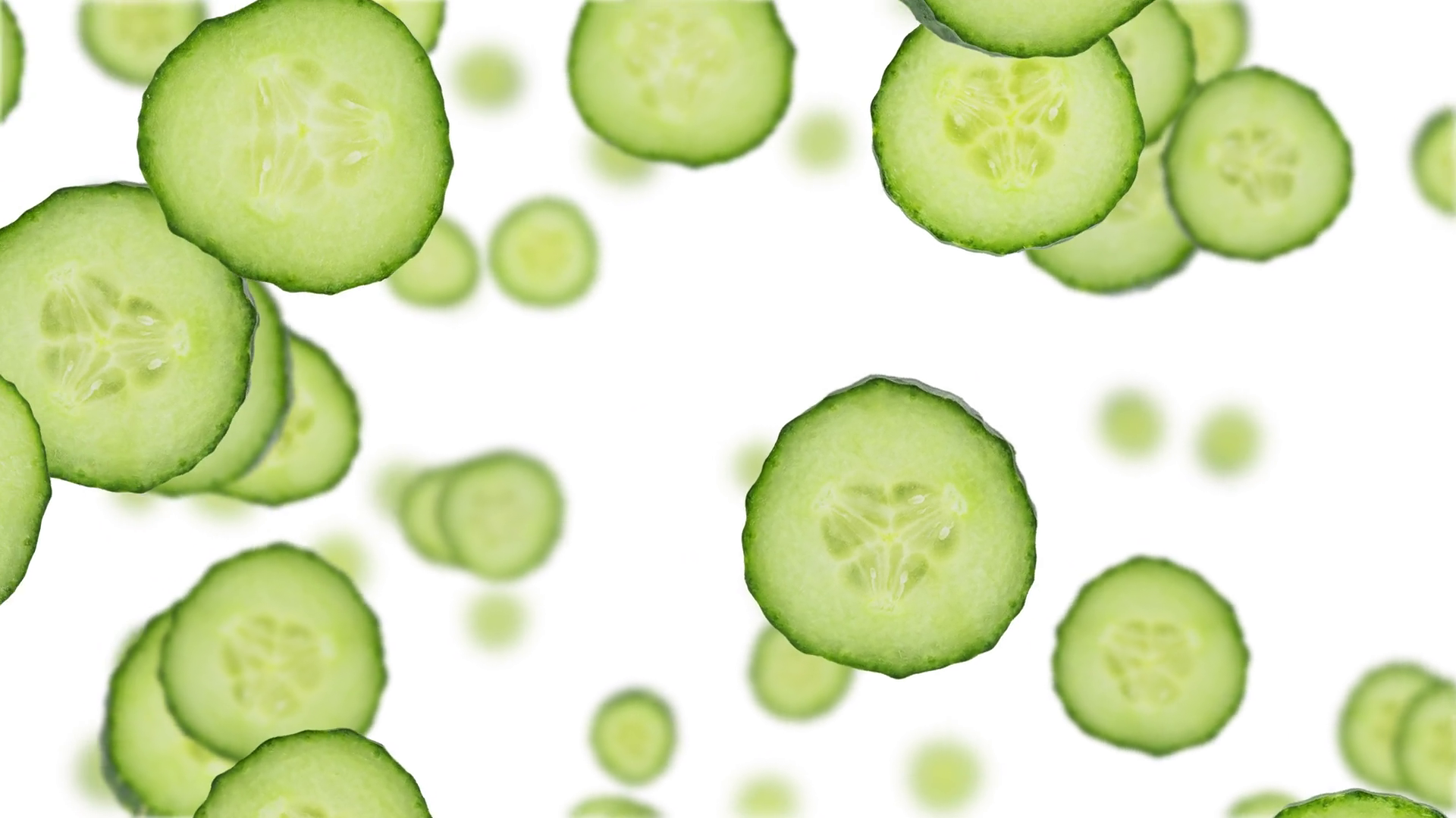 Cucumber slices falling down on white background (45 degrees ...